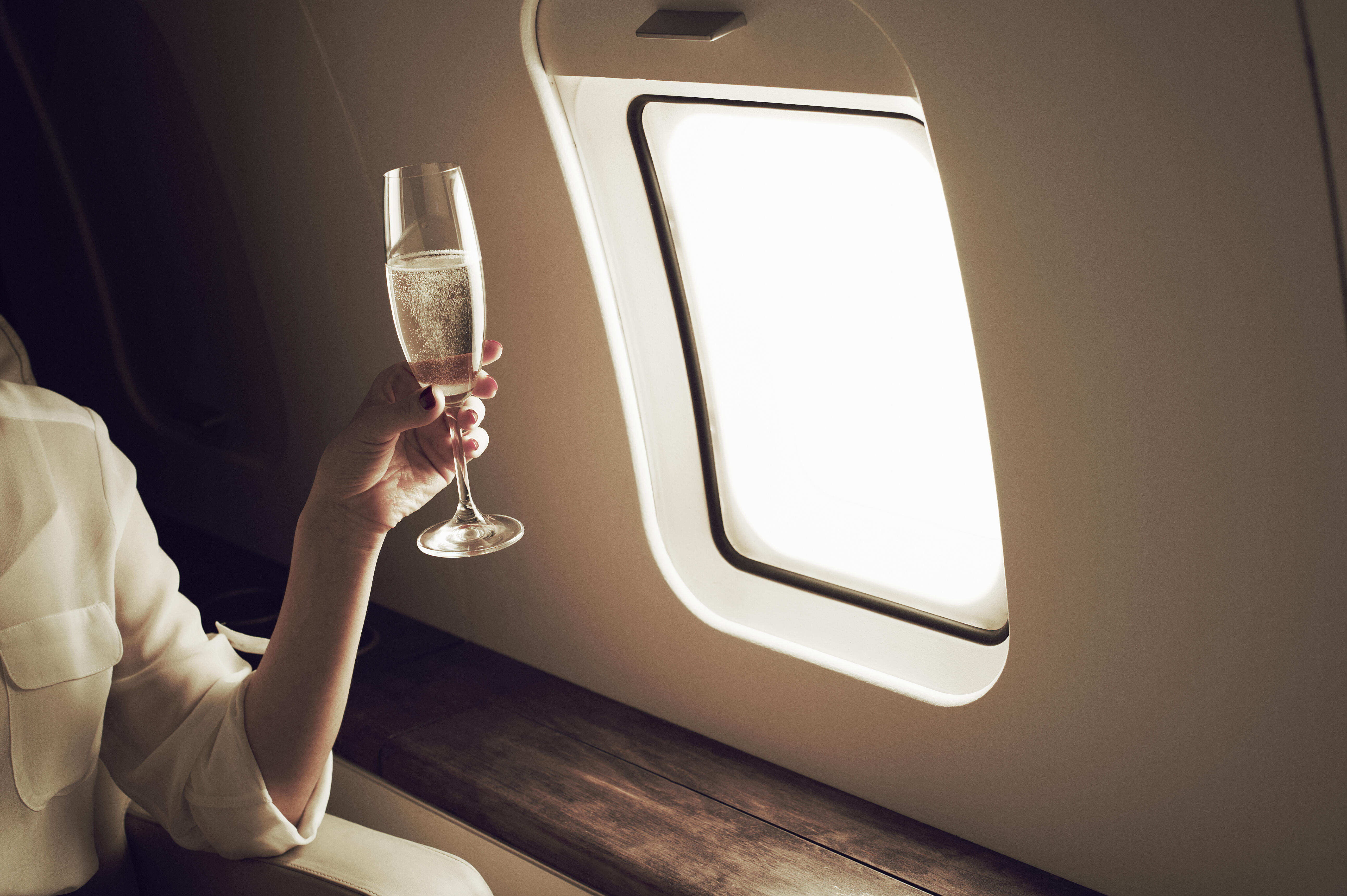 Champagne in a glass in front of an airplane window
