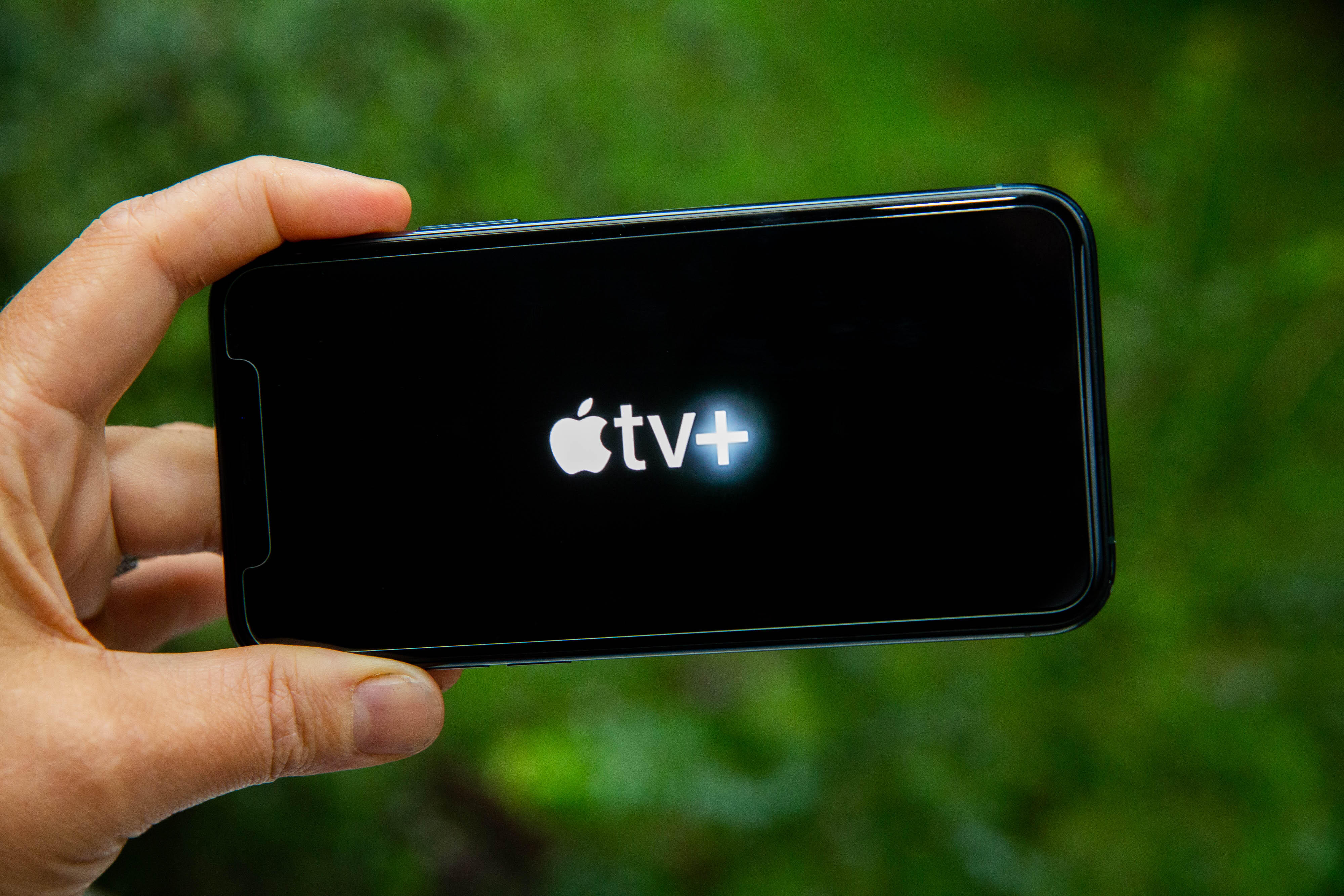 A hand holds a phone with the white Apple TV Plus logo on a black screen