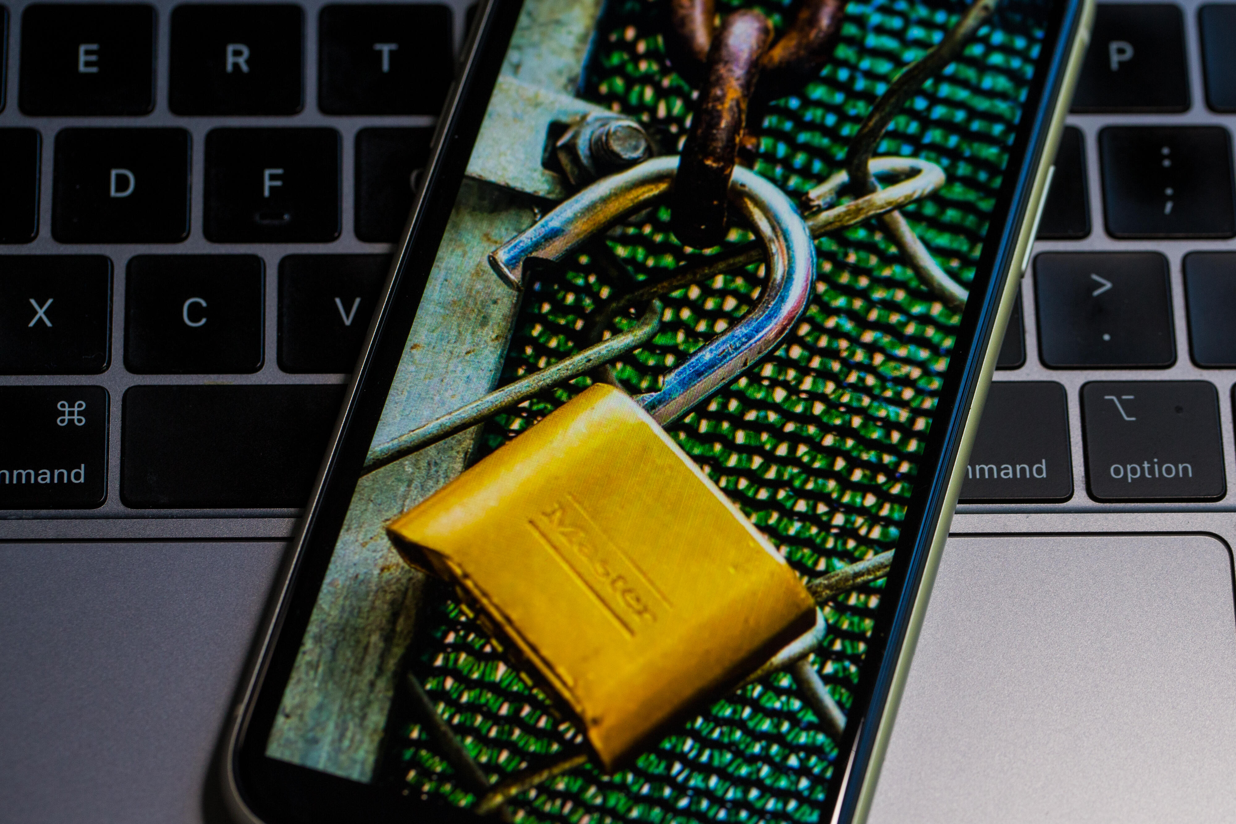 Image of a padlock and a chain-link fence on a smartphone screen.