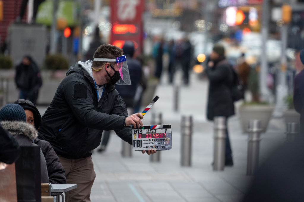 A person wearing a mask and face shield uses a clapboard during the filming of a TV series in Times Square this past March.