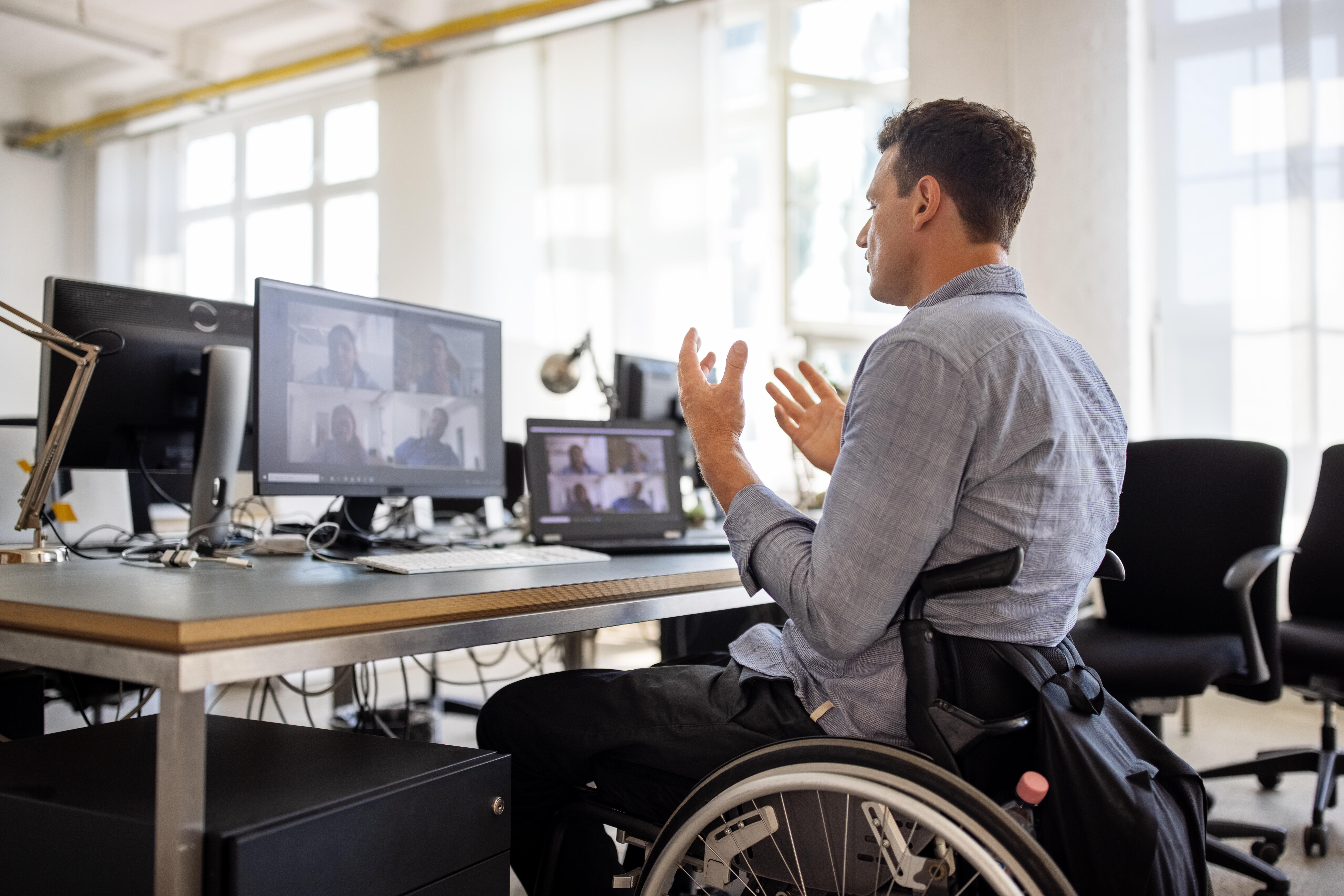 Man in wheelchair using videoconferencing on computer