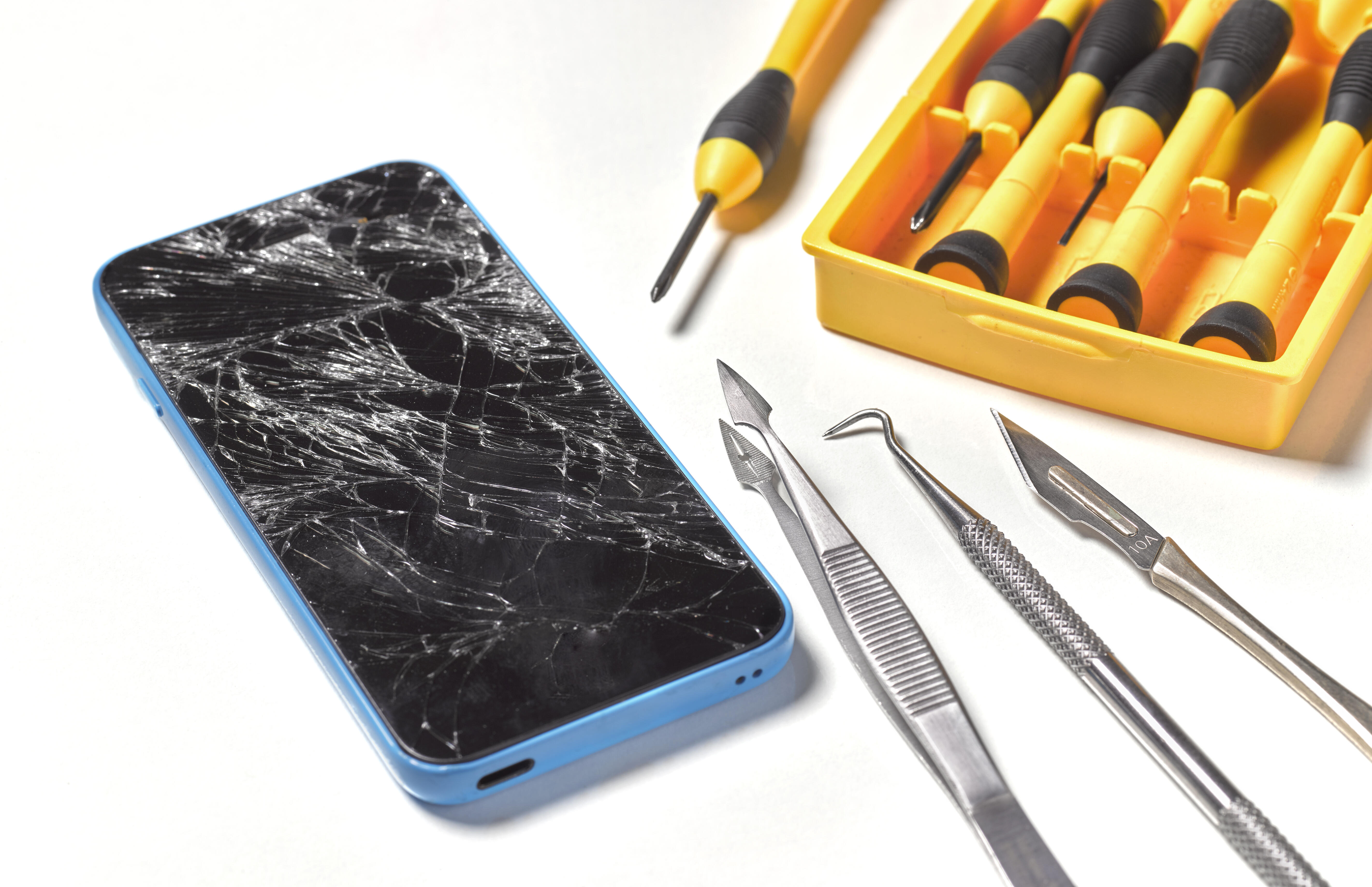 Phone with shattered screen, and a set of tools.