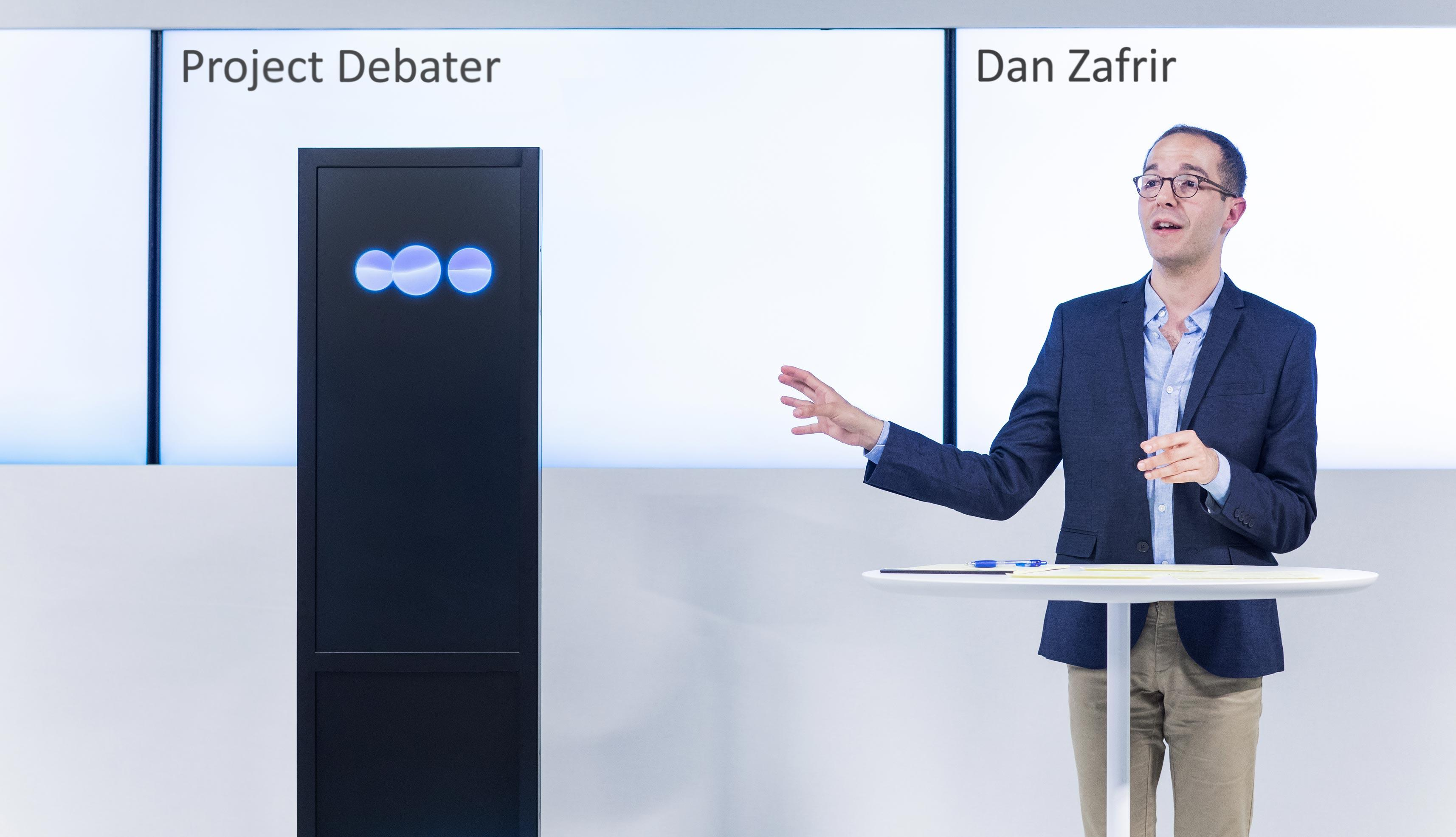 IBM Project Debater, represented by a black obelisk with animated blue circles, takes on human debater Dan Zafrir.