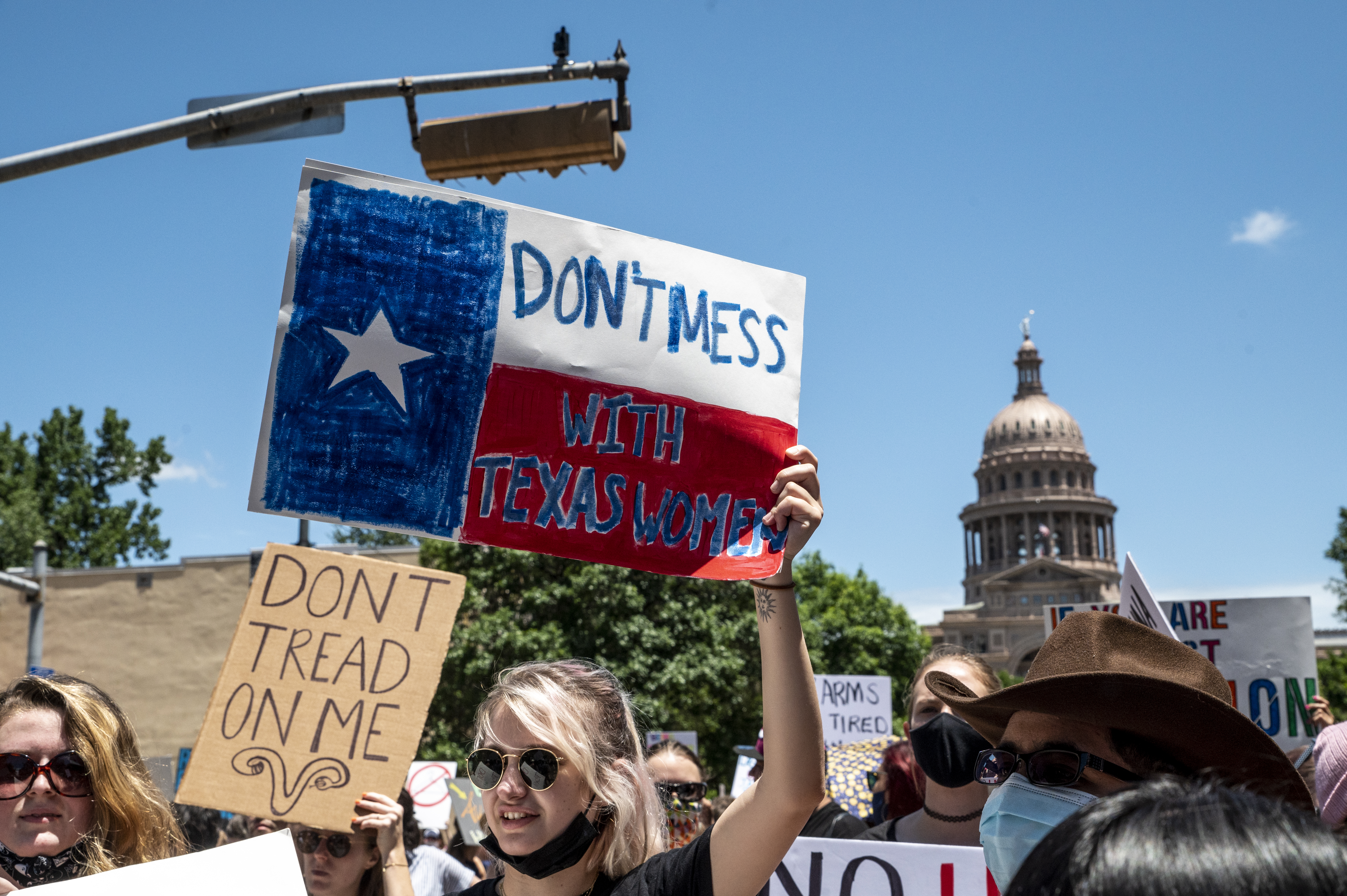 Protesters hold up signs outside the Texas state capitol in May 2021.