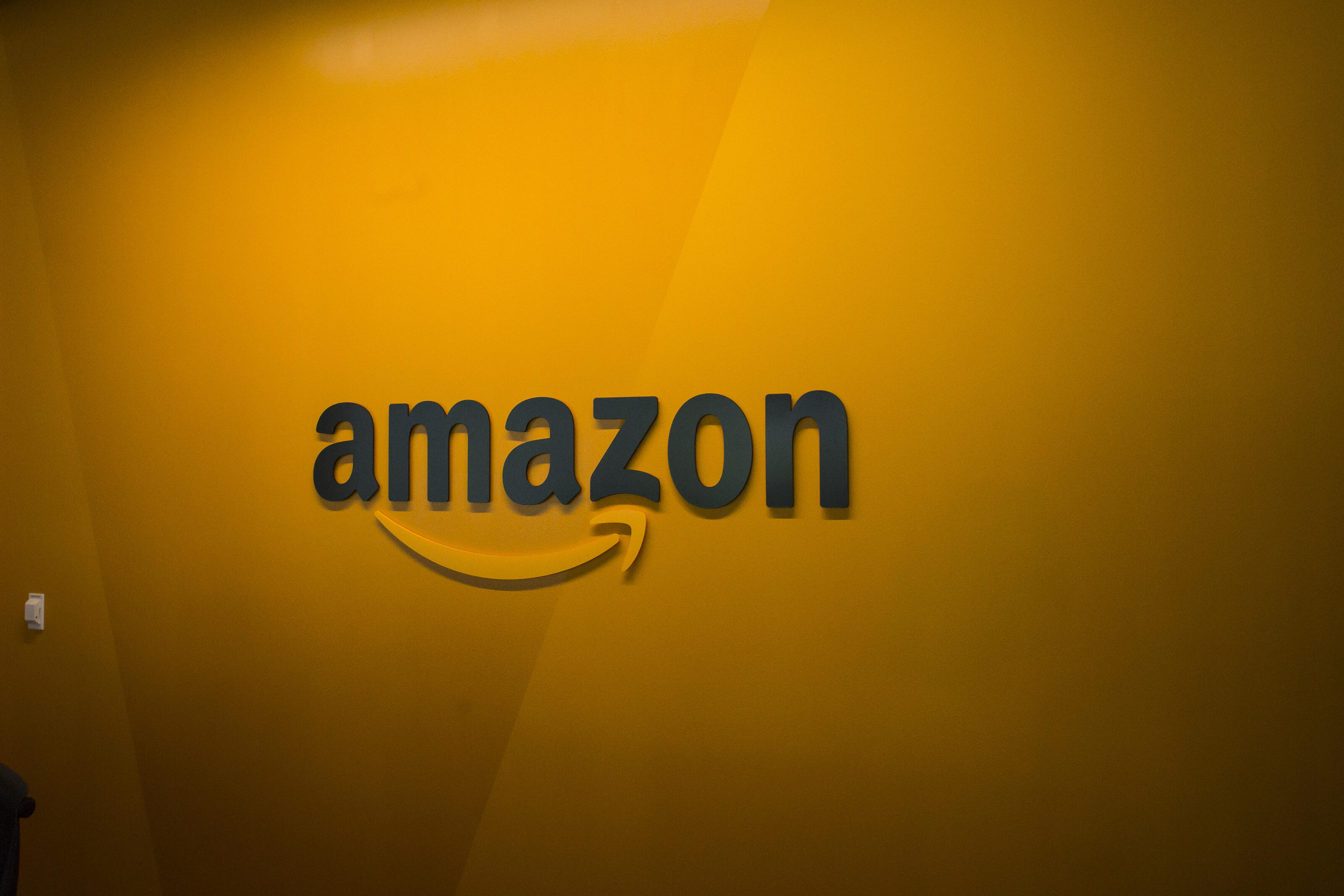 The Amazon logo on an orange wall.