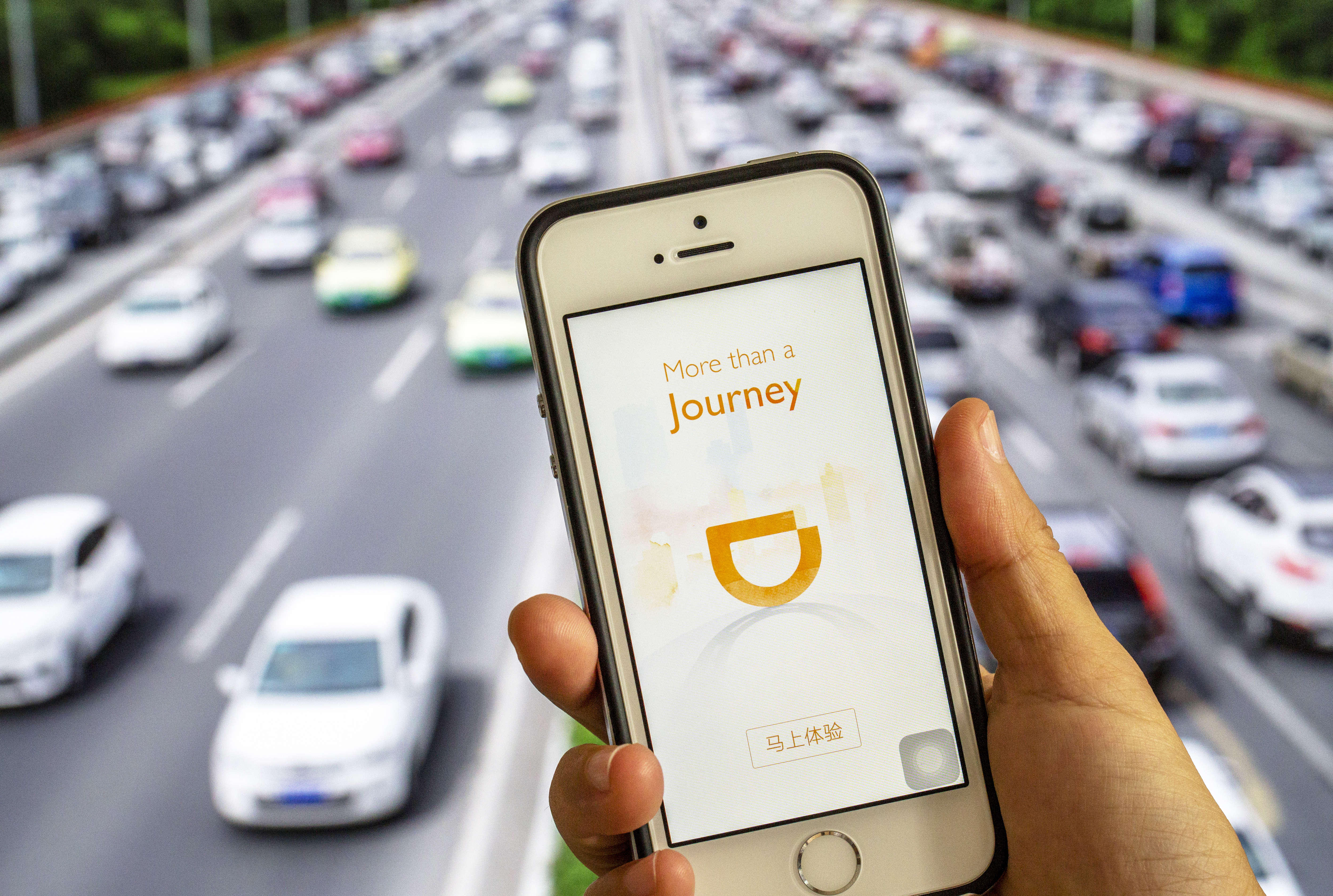 Hand holding a smart phone with an App of Didi Chuxing.