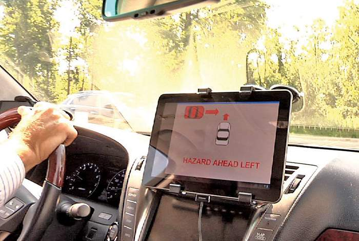 A video screen warns a driver of a potential collision ahead during a demonstration by Denso International America.