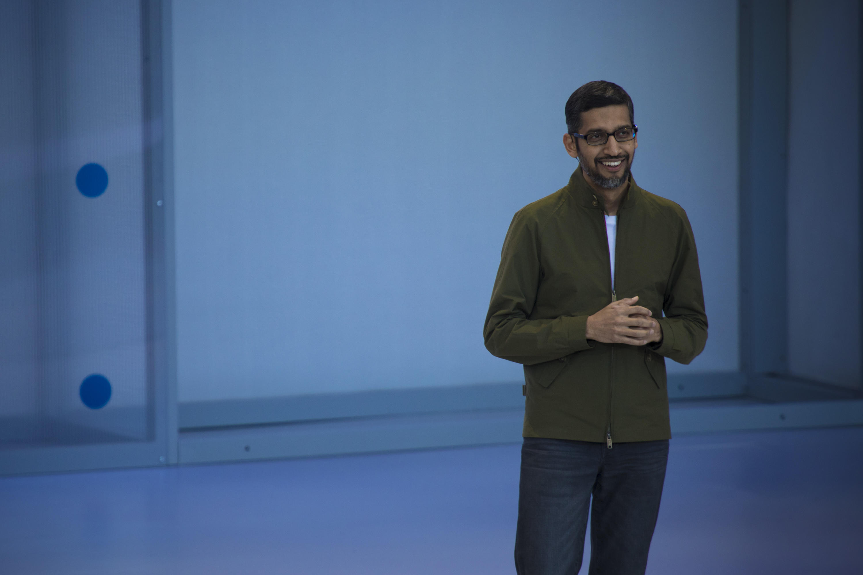 Sundar Pichai in an olive green jacket and jeans, standing onstage at the Shoreline Amphitheater Mountain View.
