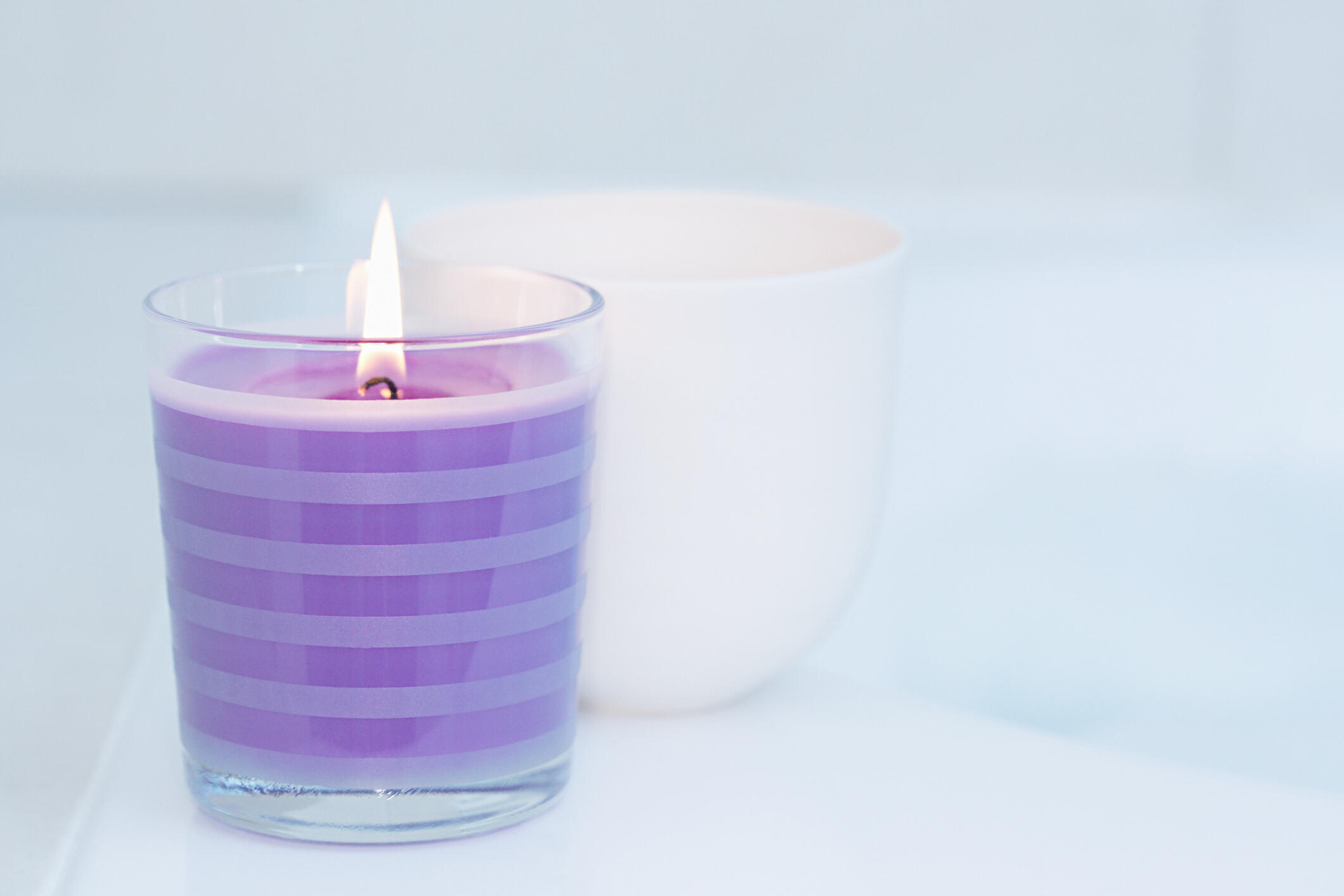 a purple candle burning on a silver background