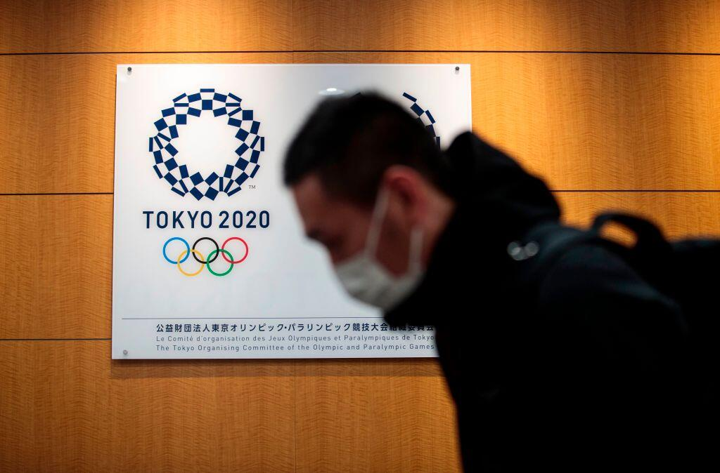 A man in a COVID mask walks by a Tokyo Olympics logo