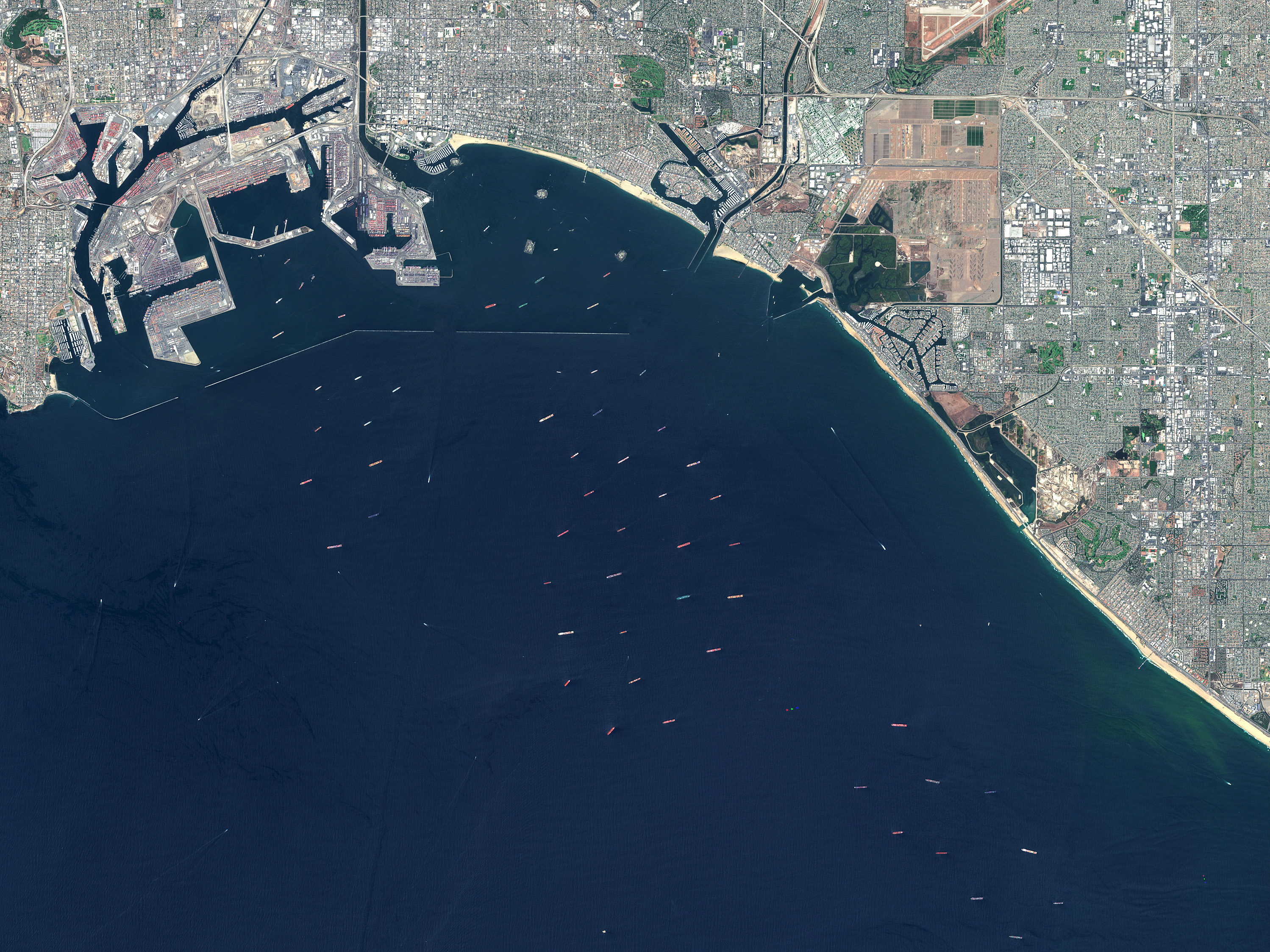 Satellite image of the ports of Los Angeles and Long Beach with dozens of ships offshore