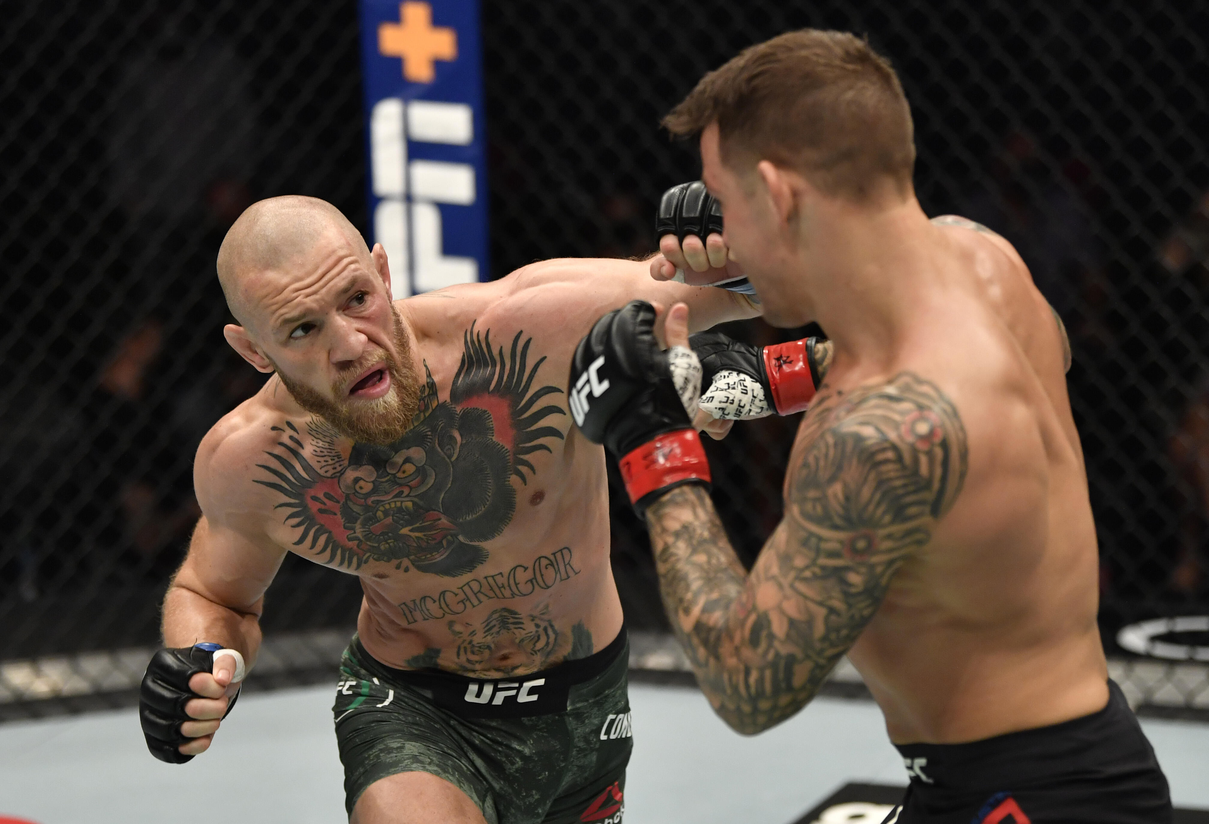 <p>Conor McGregor of Ireland punches Dustin Poirier in a lightweight fight during the UFC 257 event in January. The two meet for a rematch July 10.&nbsp;</p>