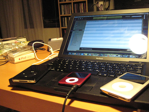Photo of laptop, iTunes, and three iPods.