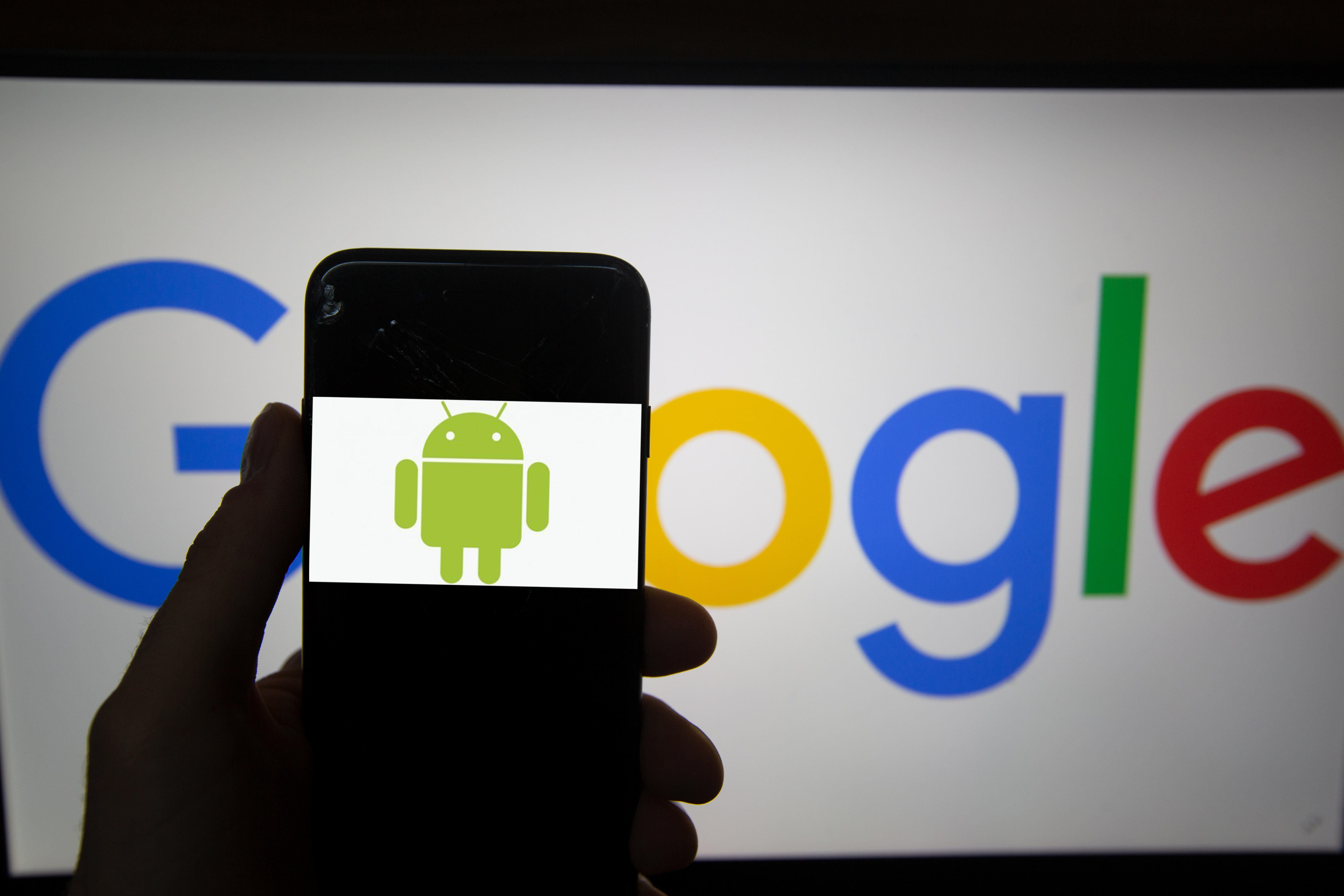 A mobile phone shows the Android logo in front of a computer monitor showing the Google logo.