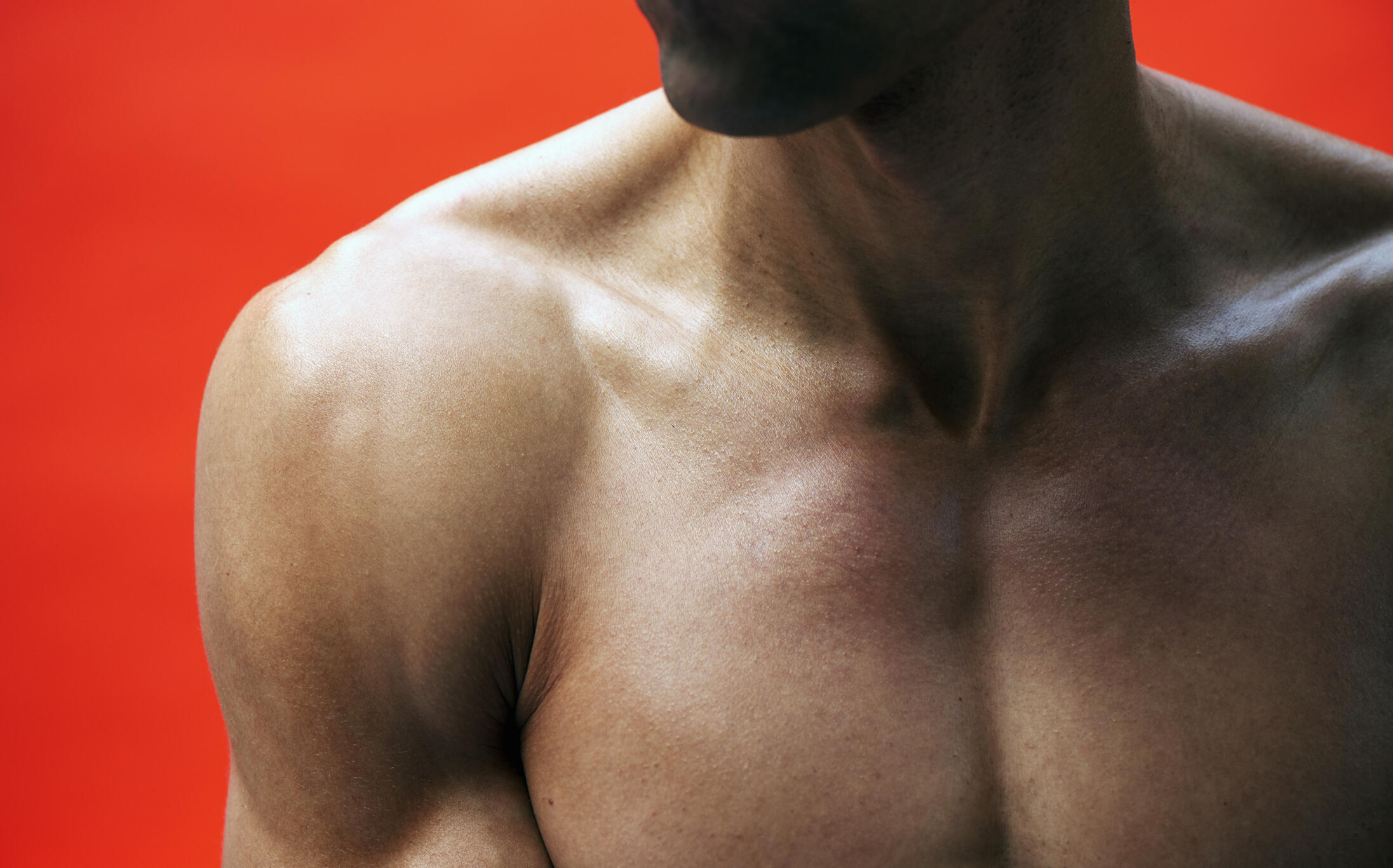 close up of a man's muscular chest on a red background