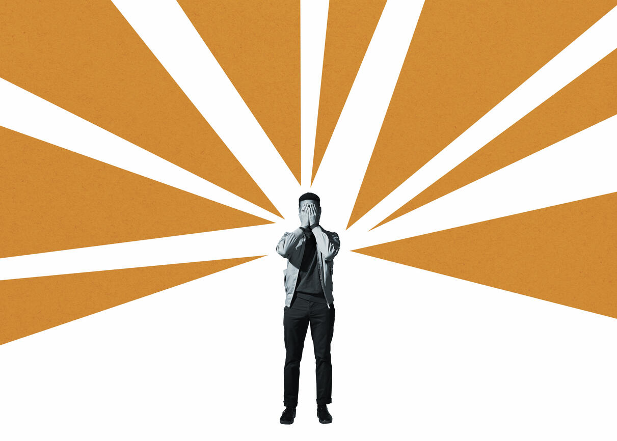 Anxious man covering face with hands while standing amidst orange rays against white background
