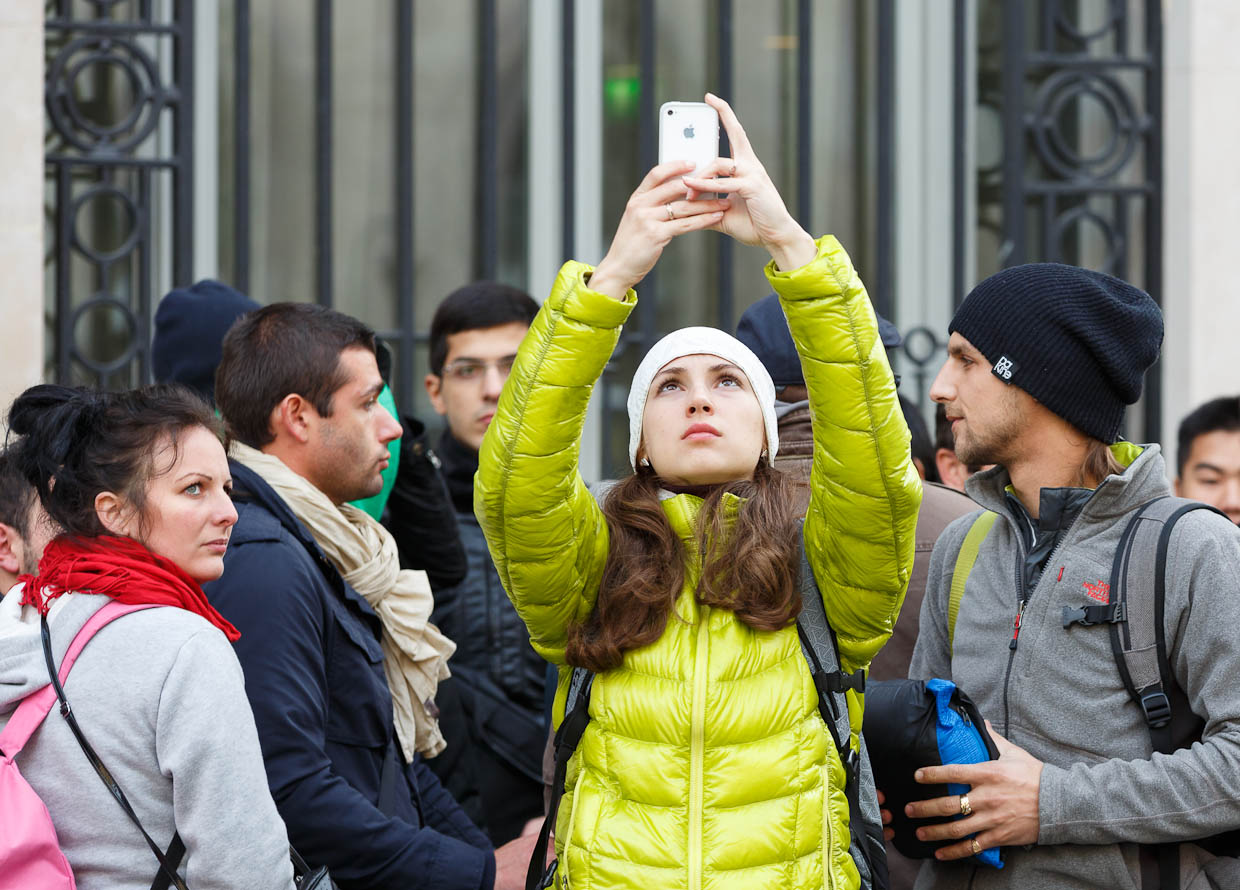 Waiting in line overnight to buy an iPhone 5 is an event to be remembered, not a mere purchase. Here, one customer in Paris uses her older iPhone to take a sweeping video of the line and the store.