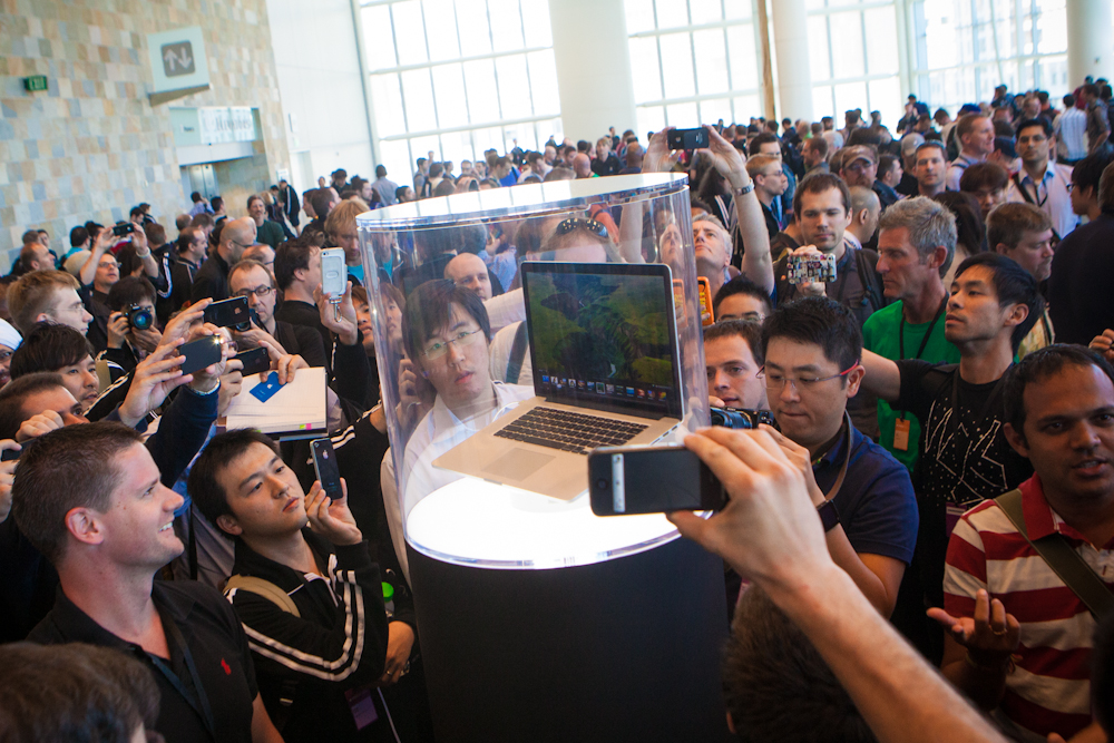 WWDC attendees crowding around enclosed versions of Apple's latest MacBook.