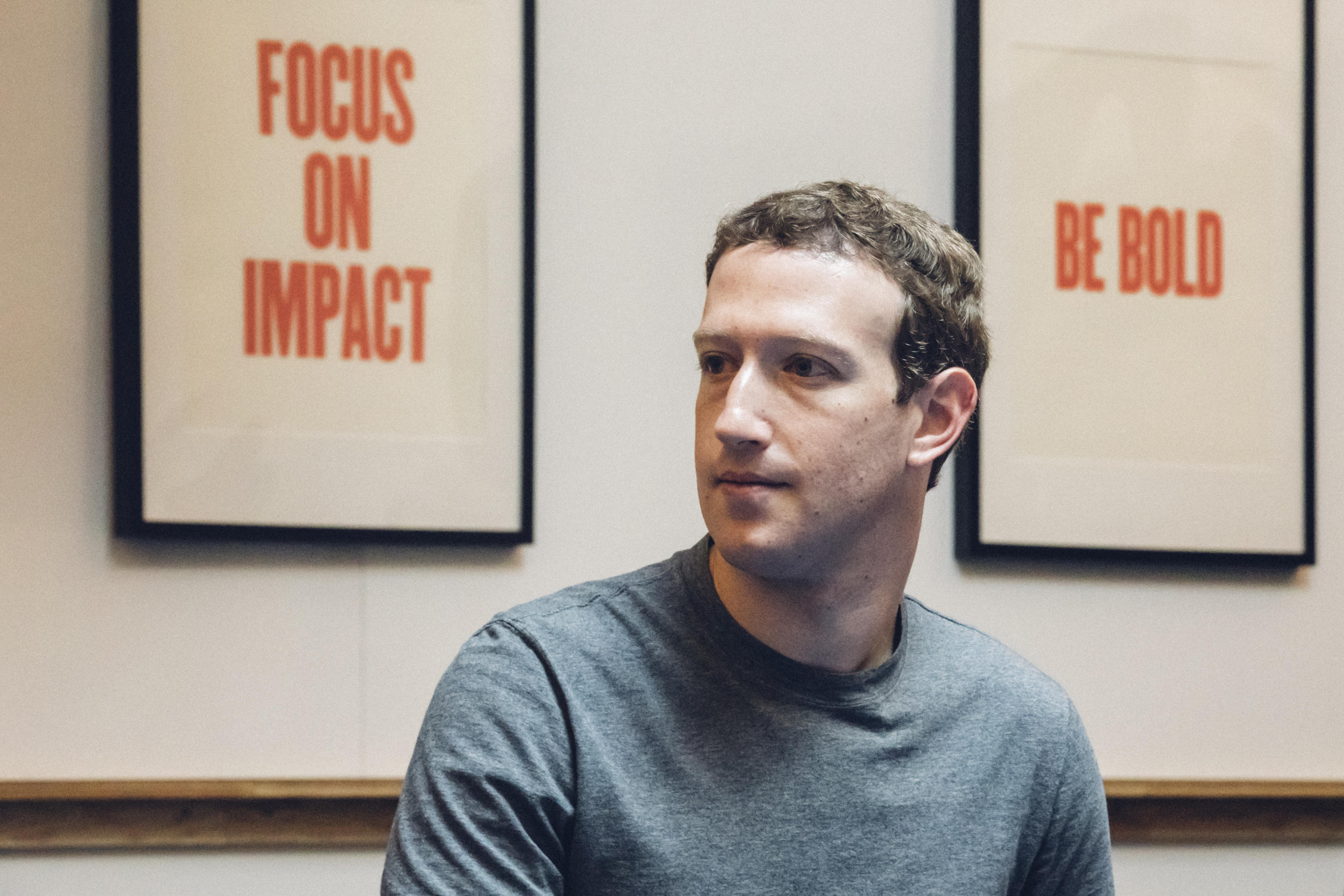 """Facebook CEO Mark Zuckerberg, in front of signs that say """"Focus on Impact"""" and """"Be Bold."""""""