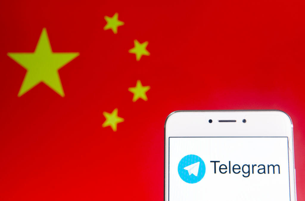 Illustration of the Telegram app on a mobile phone screen in front of the flag of China.