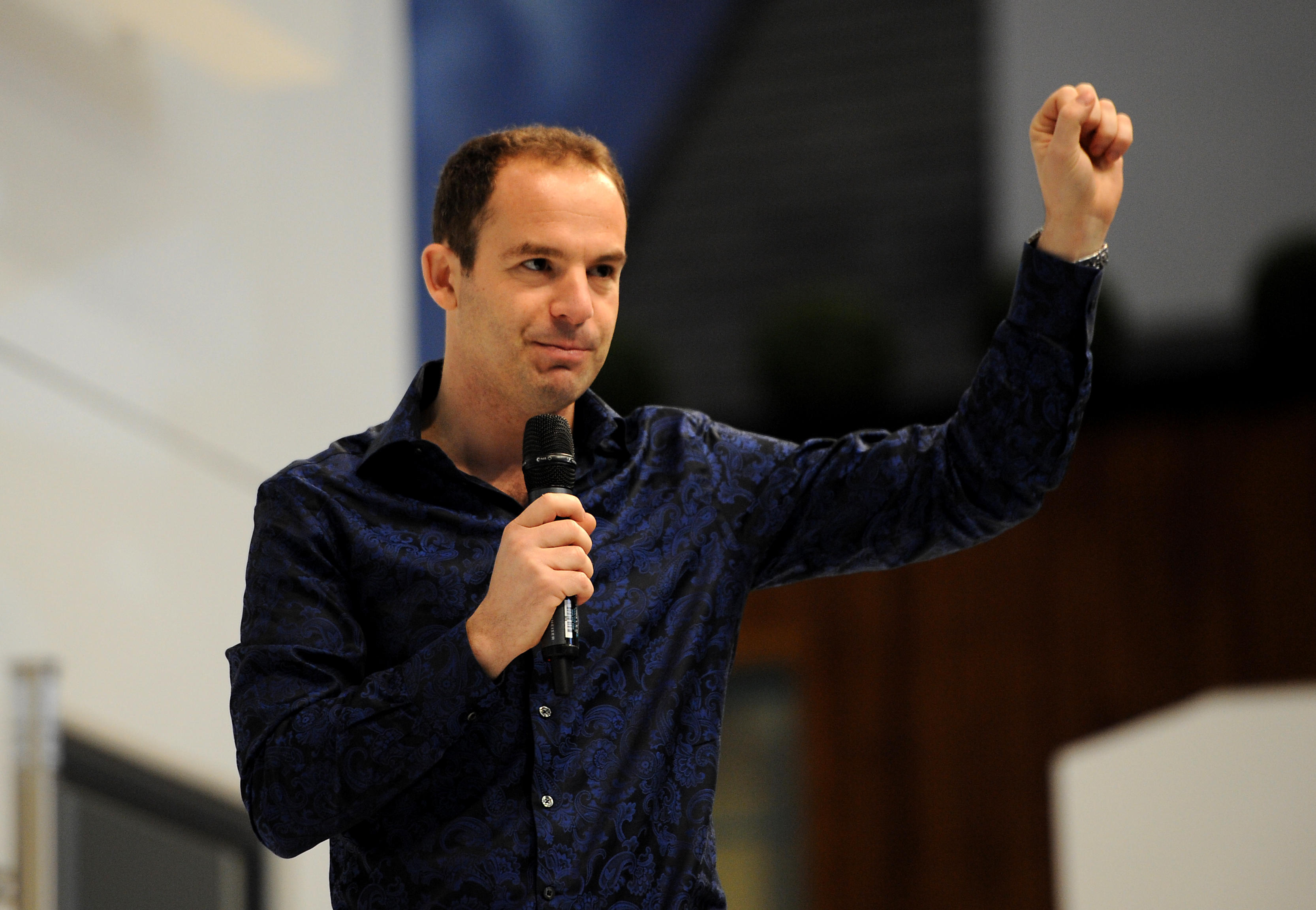 A medium-distance photo of Martin Lewis in a dark blue button down shirt and holding a microphone in his right hand while holding up his right fist.