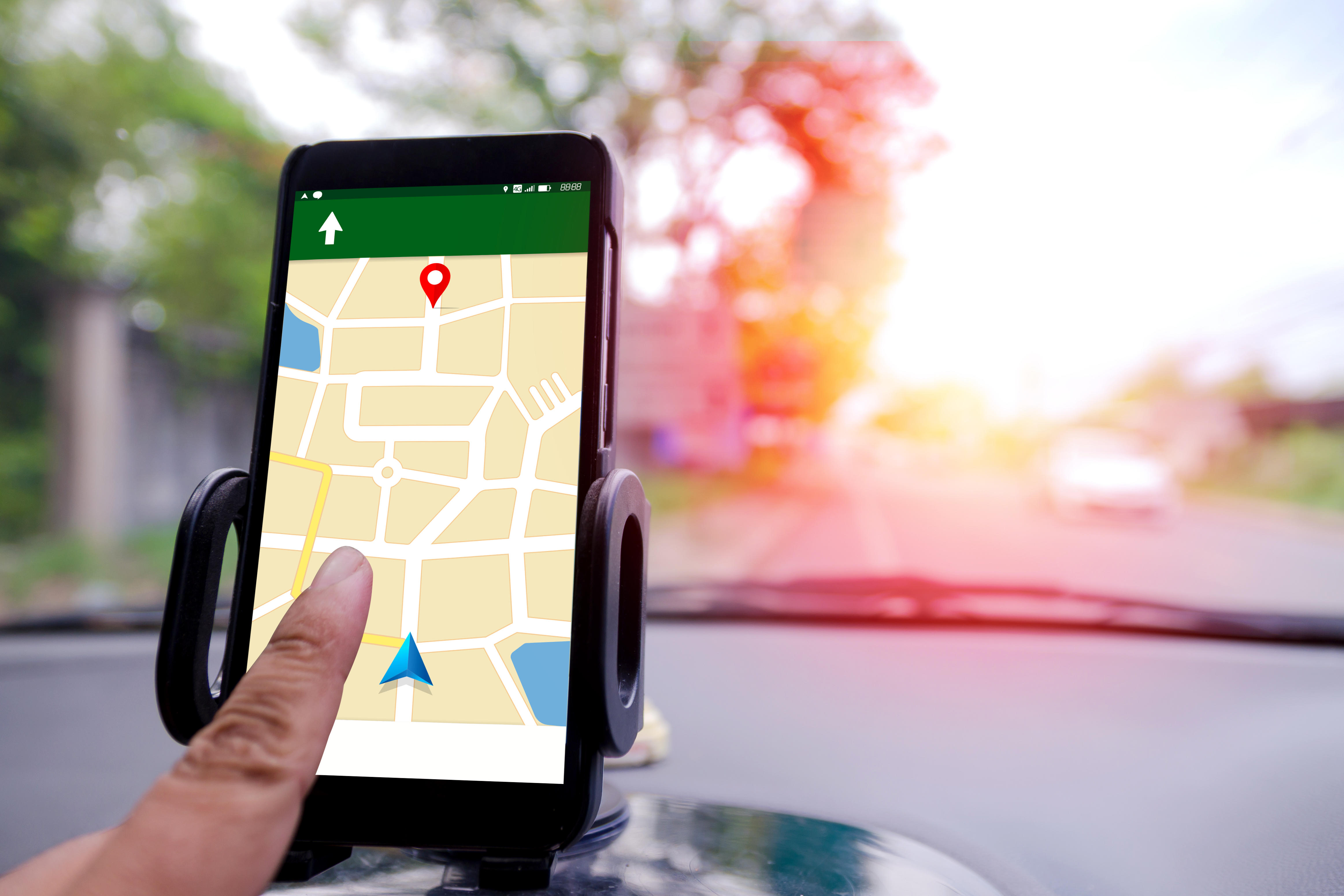 Close-Up Of Hand Operating Global Positioning System On Smart Phone In Car