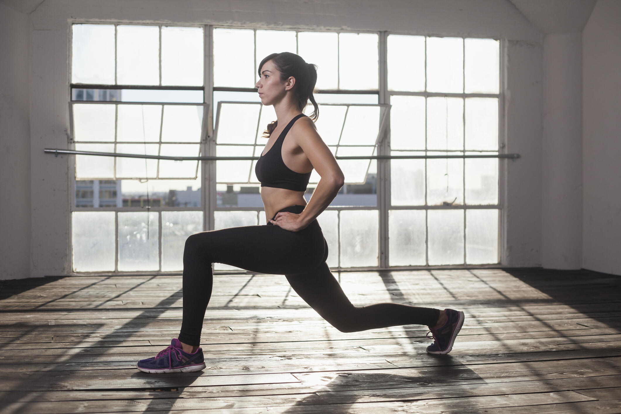 A woman in black fitness leggings and a black sports bra doing lunges in an empty studio.