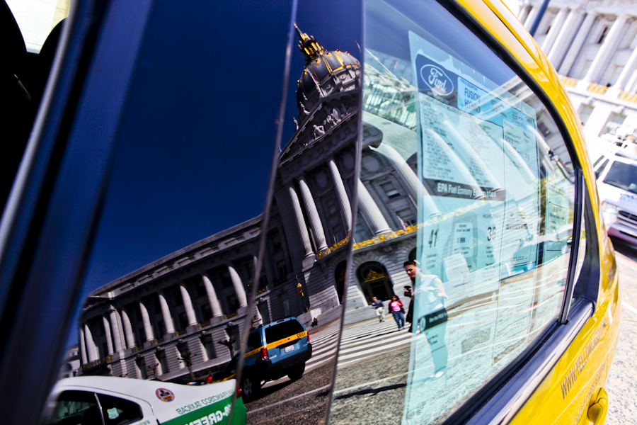 San Francisco City Hall is reflected in the window of a Ford Fusion Hybrid during Mayor Gavin Newsom's announcement that the more than half of the city's cabs now run on alternative fuels.