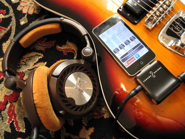 Photo of the Sonoma Wire Works GuitarJack recording accessory for iPhone, along with a guitar and headphones.