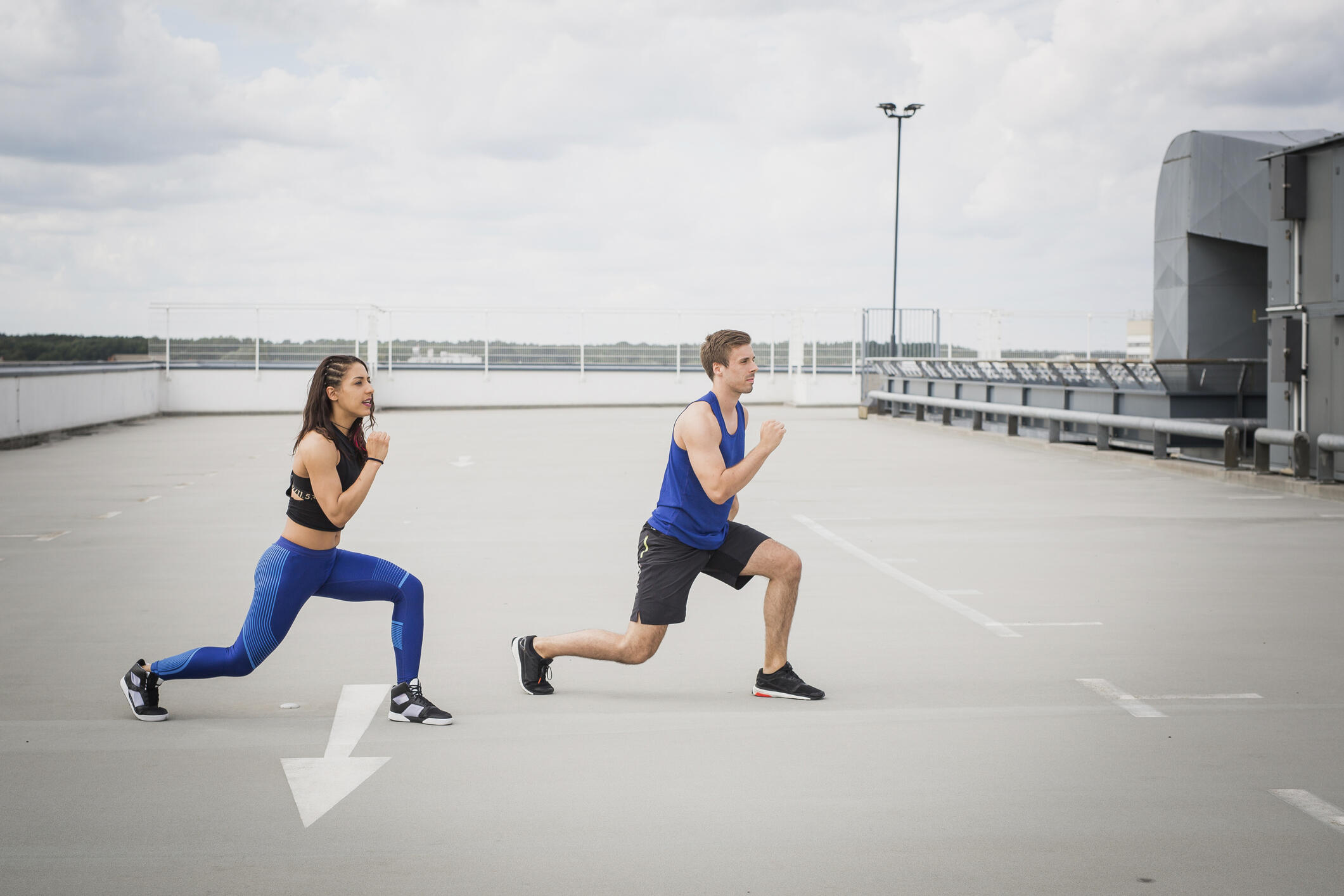 A young woman and man do lunges in a rooftop parking lot