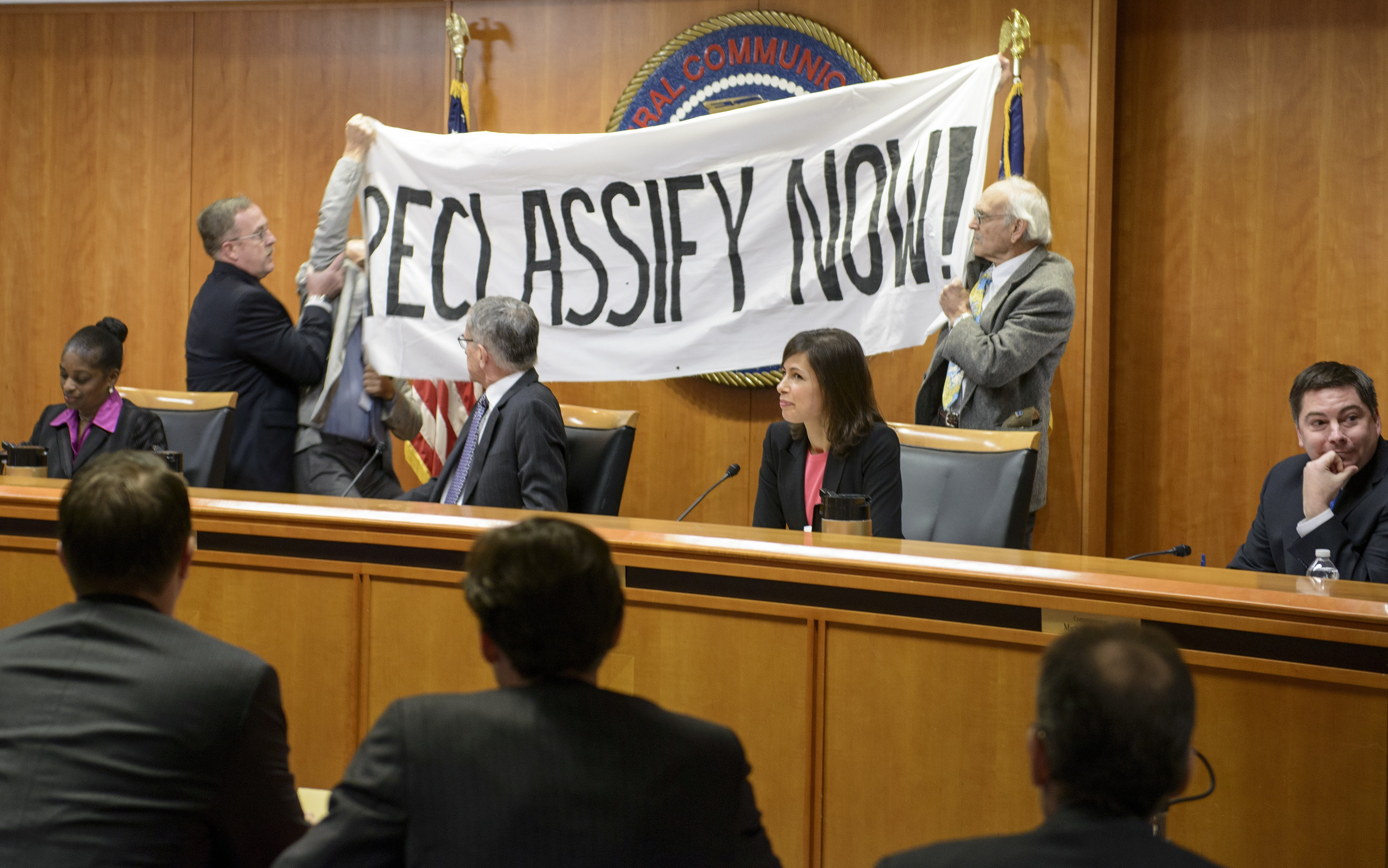 From left to right: Commissioner Mignon Clyburn, Chairman Tom Wheeler, Commissioner Jessica Rosenworcel and Commissioner Michael O'Rielly watch as pro-Net neutrality protesters are removed from the dais during a hearing at the FCC this past December.