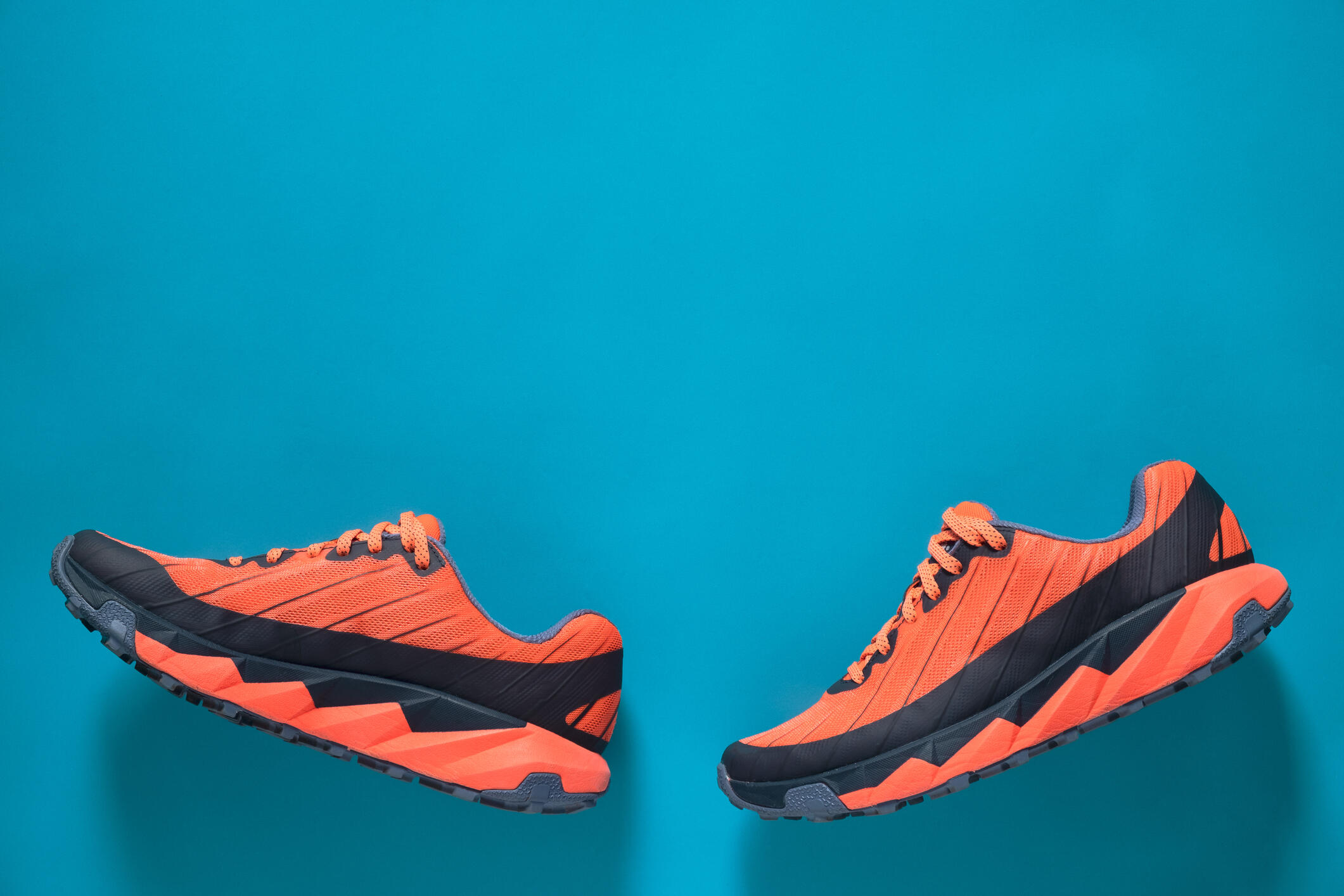Orange and black running shoes on a bright blue background