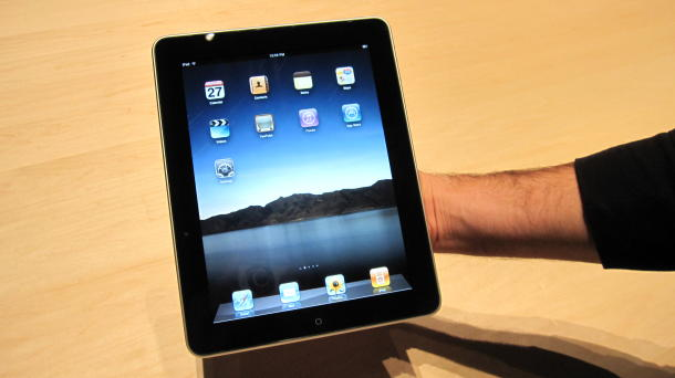 Photo of iPad being held in one hand.