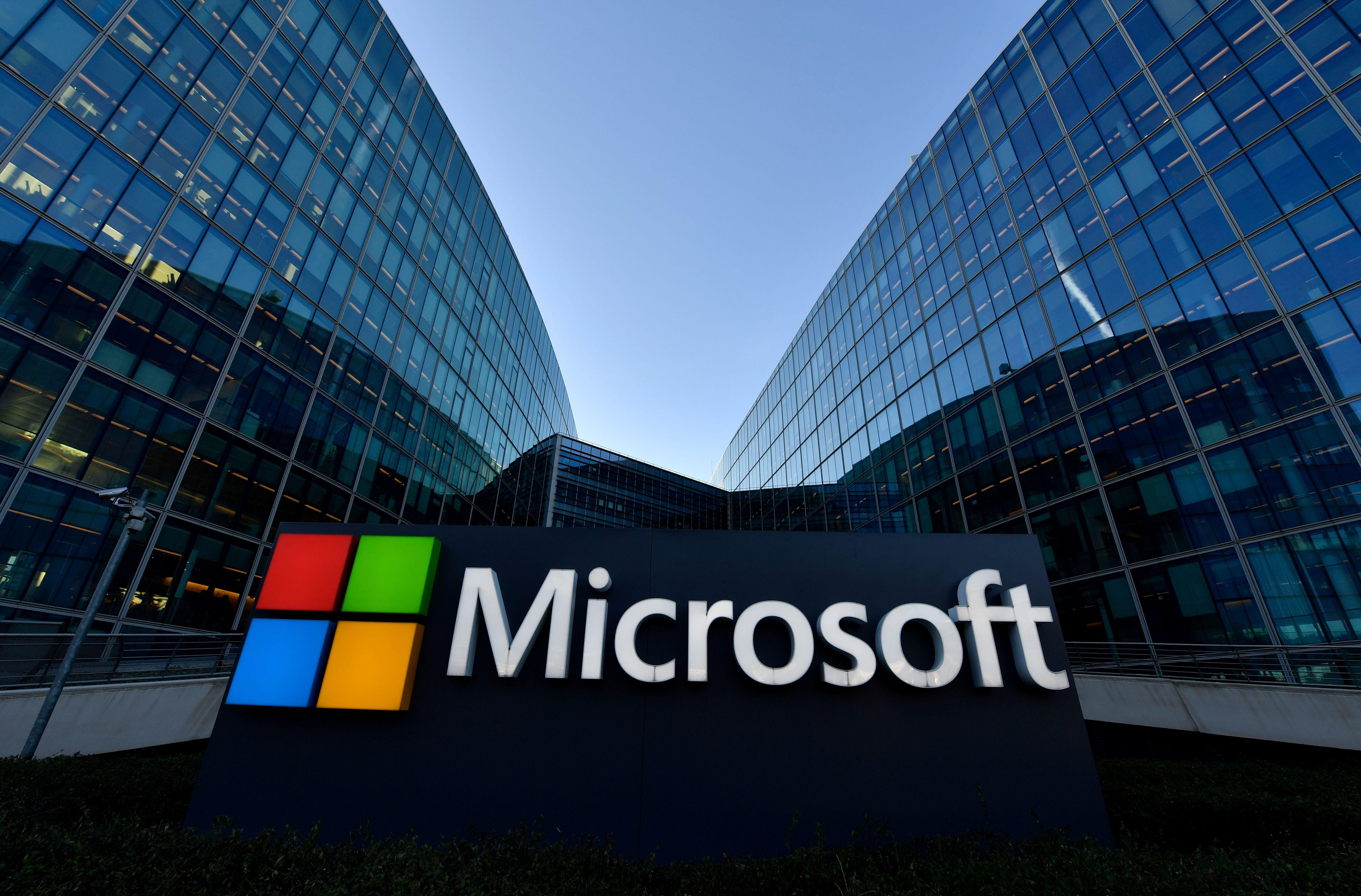 Microsoft logo on sign in front of steel and glass buildings.