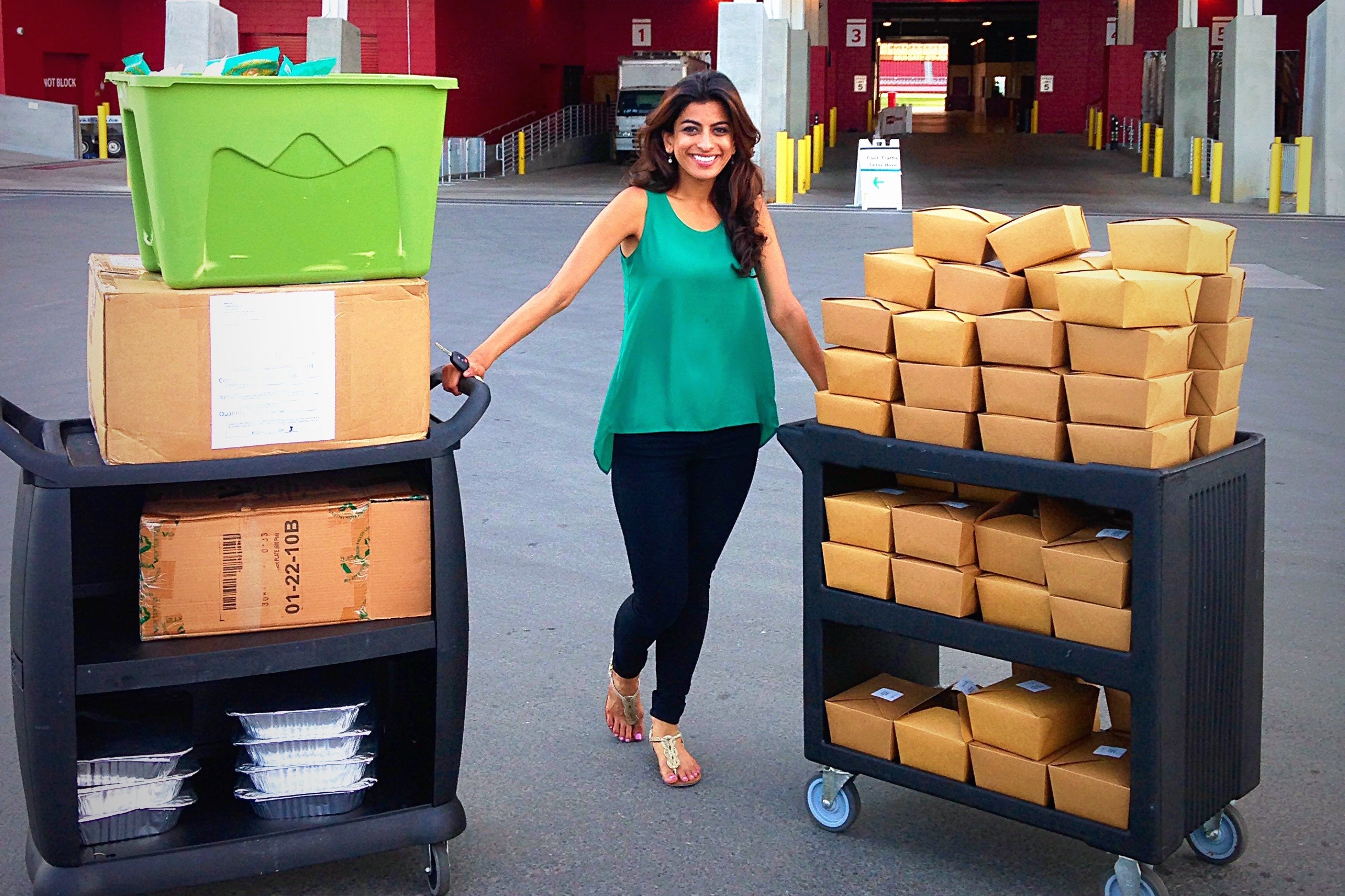 Feeding Forward CEO Komal Ahmad shows off surplus food collected from the Bite Silicon Valley food-tech conference in early June. Leftovers gathered at this event fed more than 4,279 people at eight different shelters and food banks.