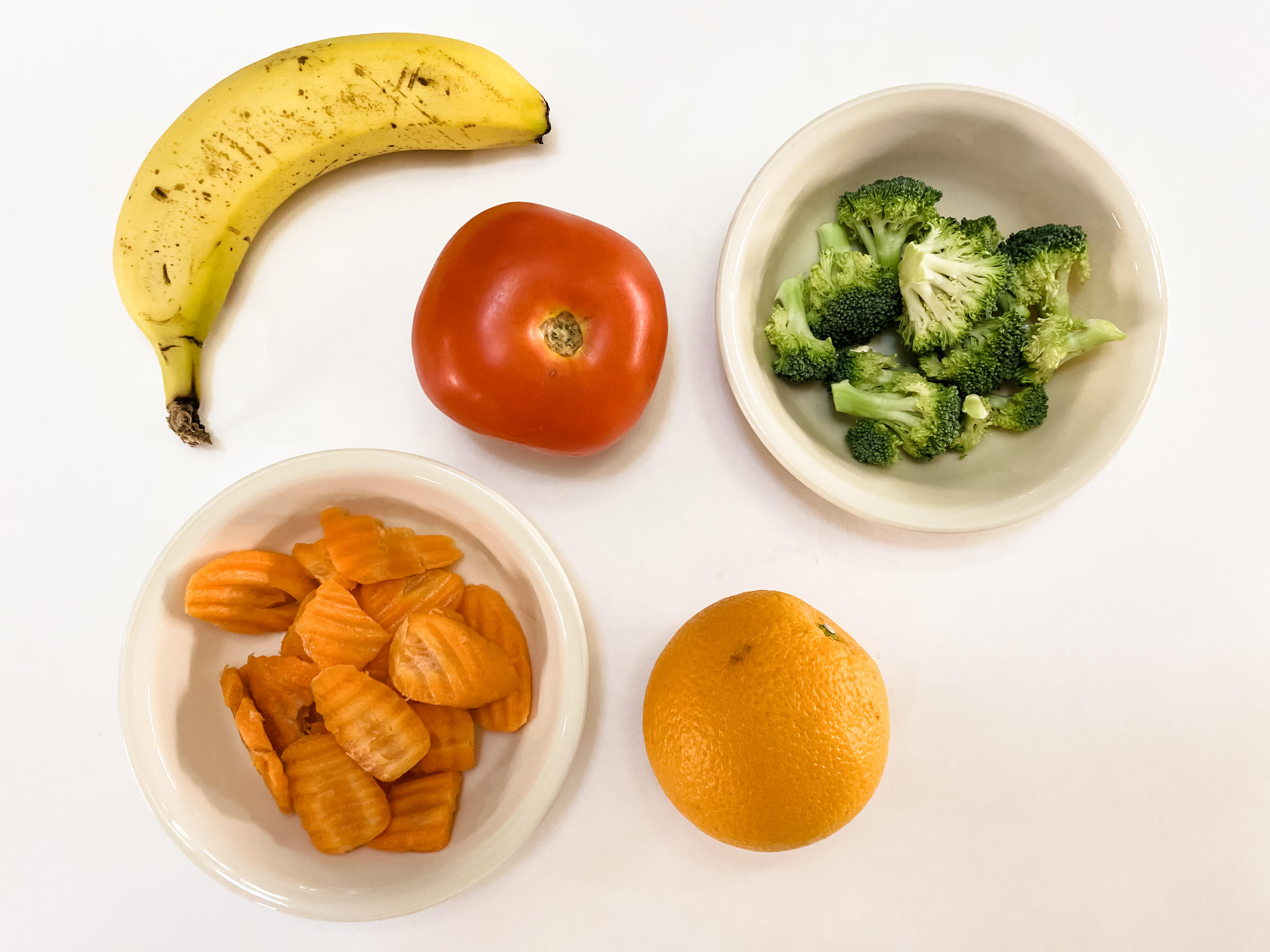 Five servings of produce: a medium banana, a tomato, an orange, half a cup of broccoli, and half a cup of carrots.