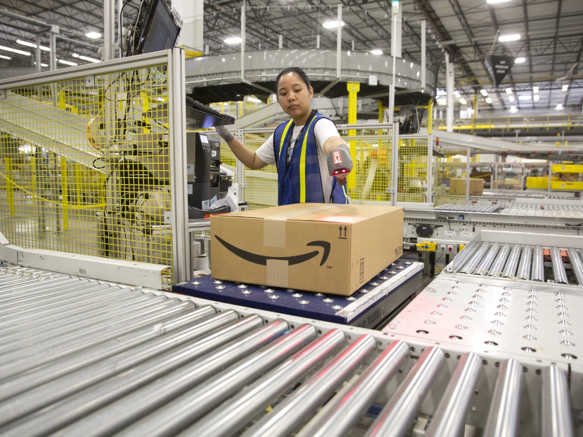 """A worker at Amazon's shipping center in Schertz, Texas. The center includes a proprietary """"robo-stow"""" robotic arm system. Five hundred humans work there full-time too."""