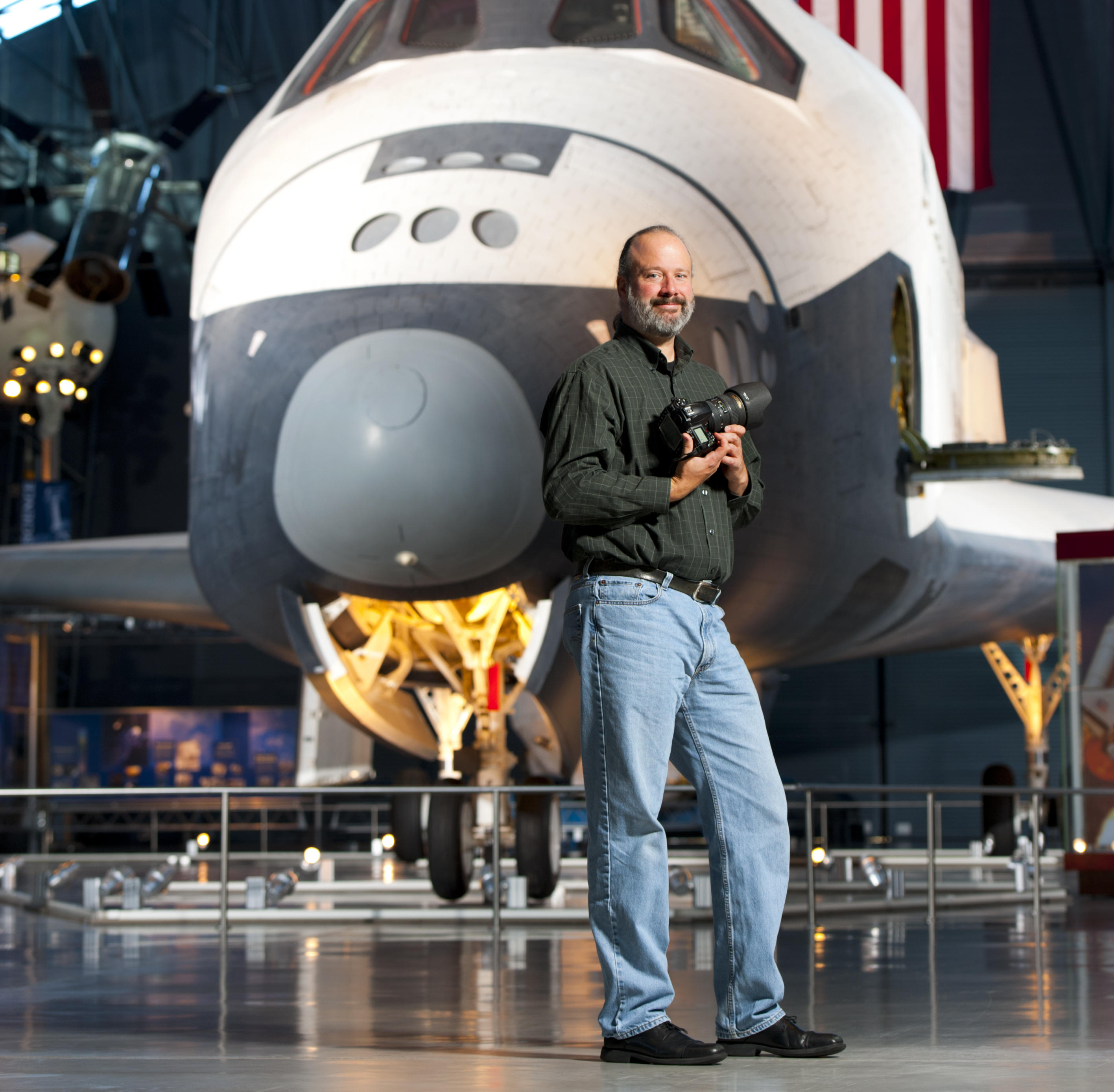 NASA photographer Bill Ingalls stands in front of a space shuttle.