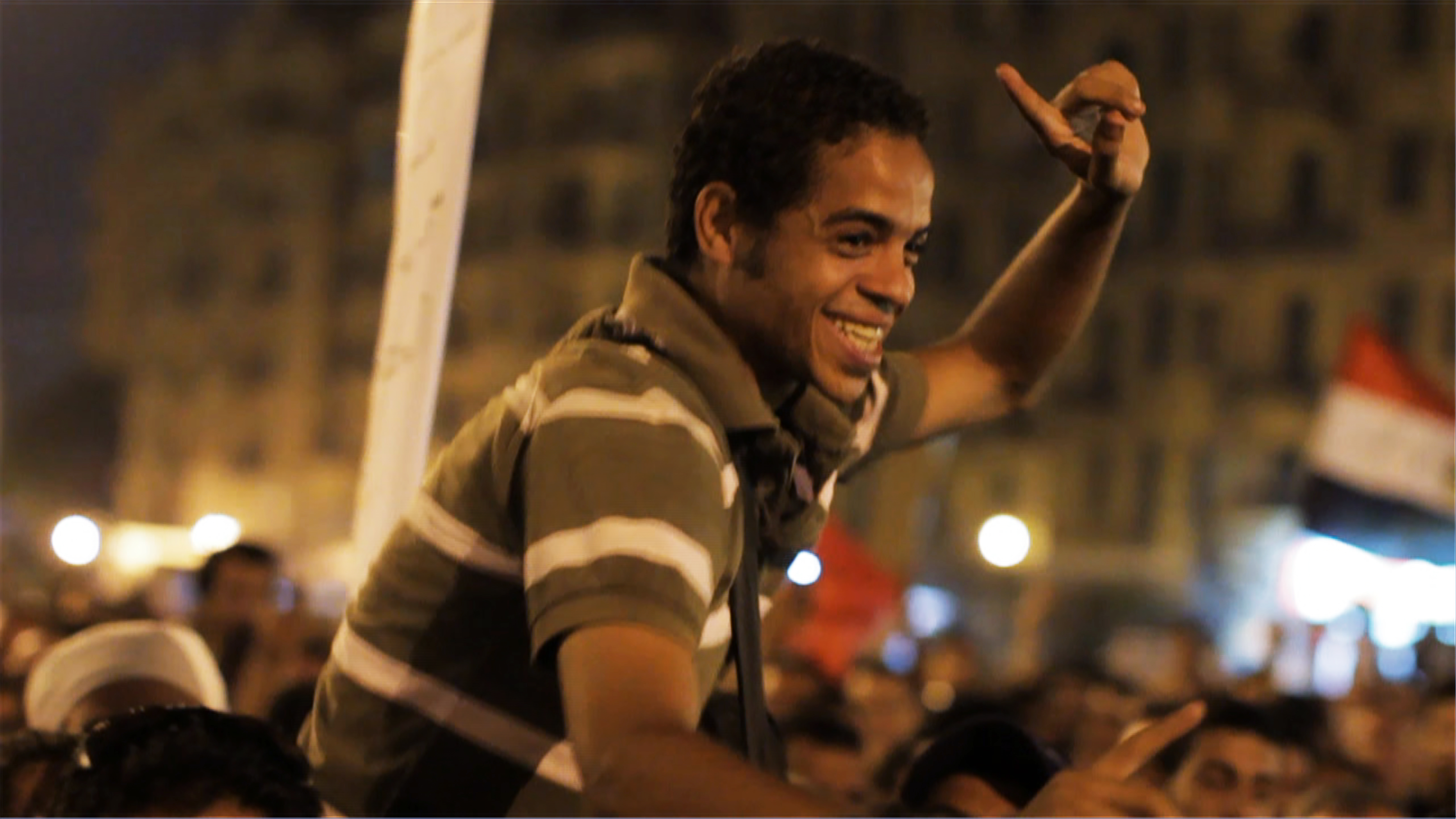 A young activist held aloft by Egyptians protesting