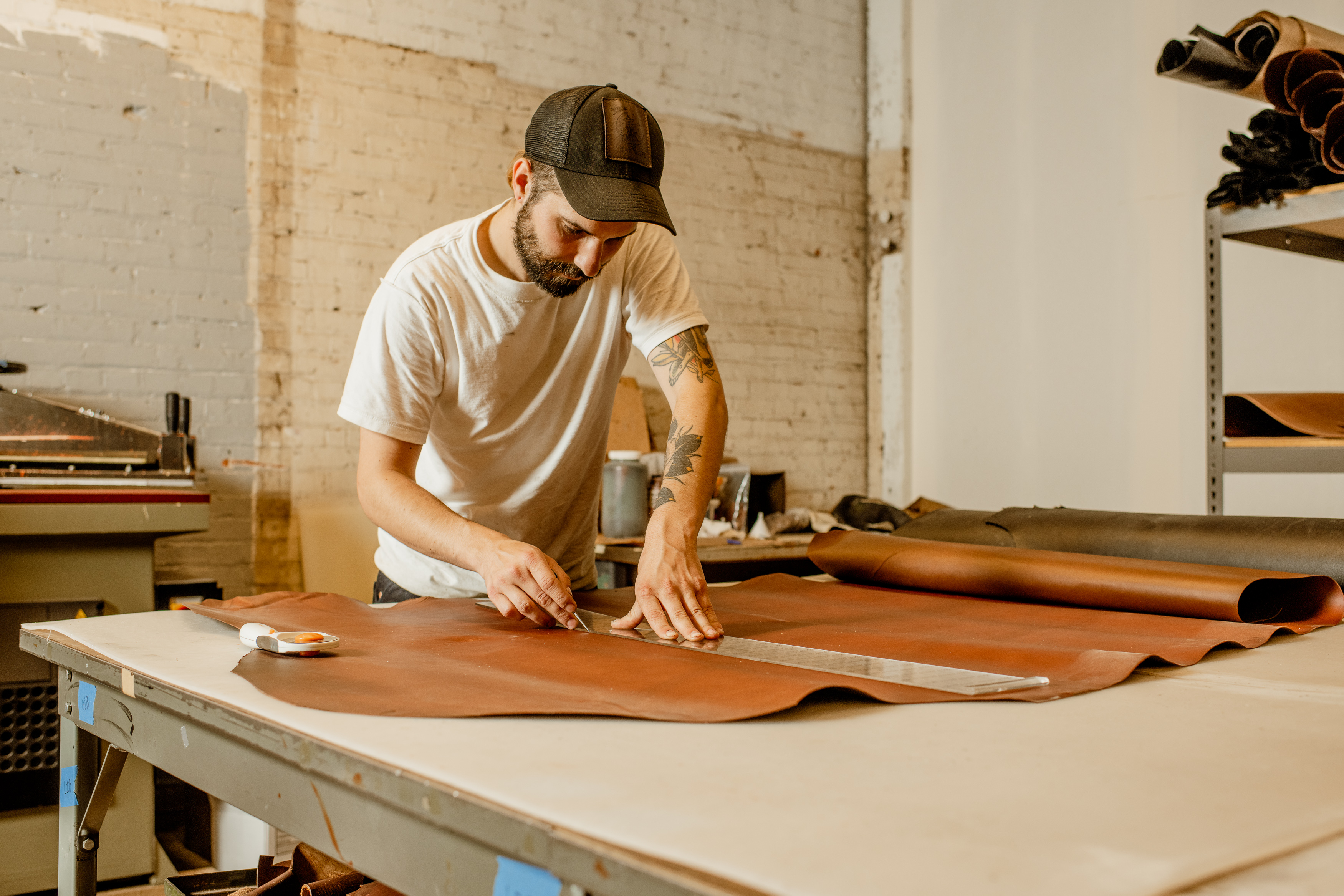 A worker prepares leather to be cut into a pattern at specialty leather goods maker Hardmill
