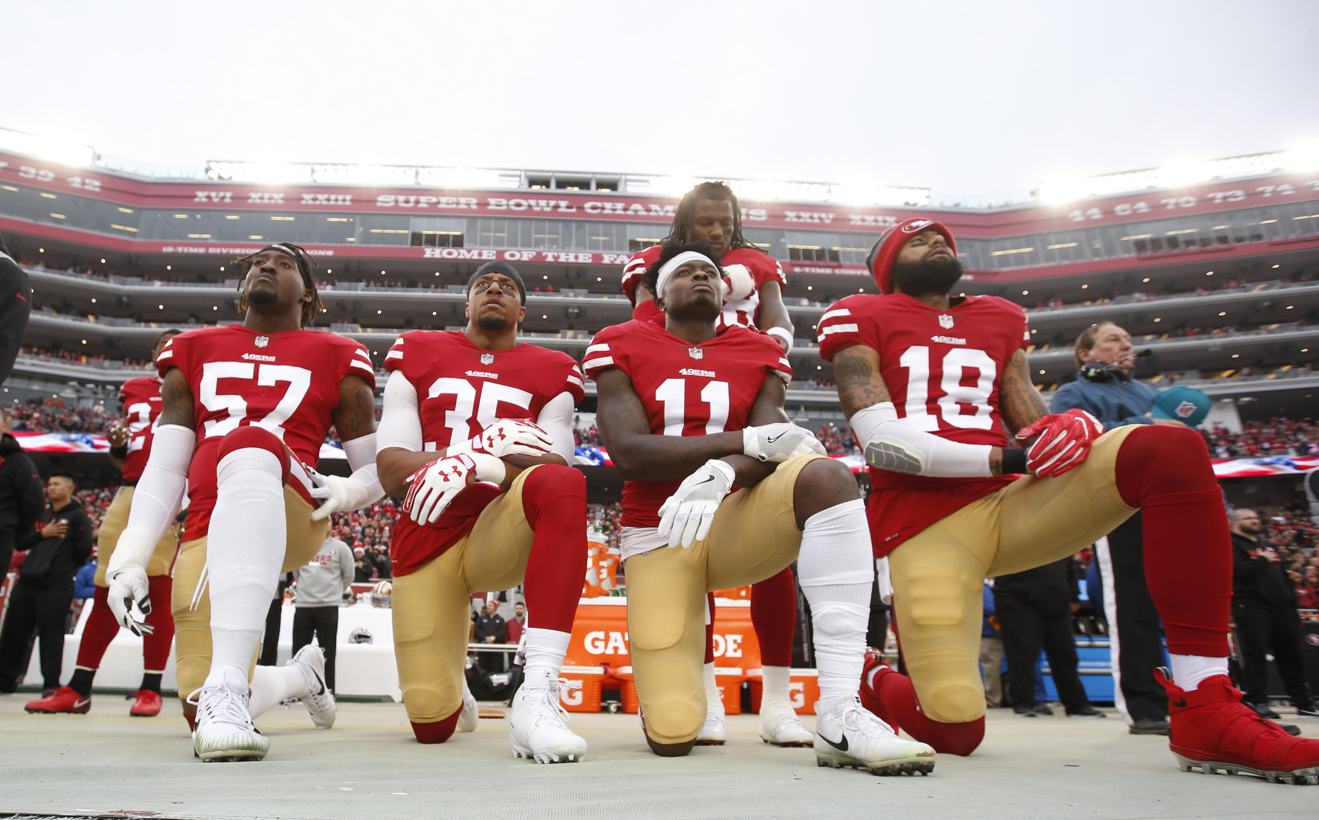 San Francisco 49ers players kneel on the sideline as the national anthem plays before a game last December.