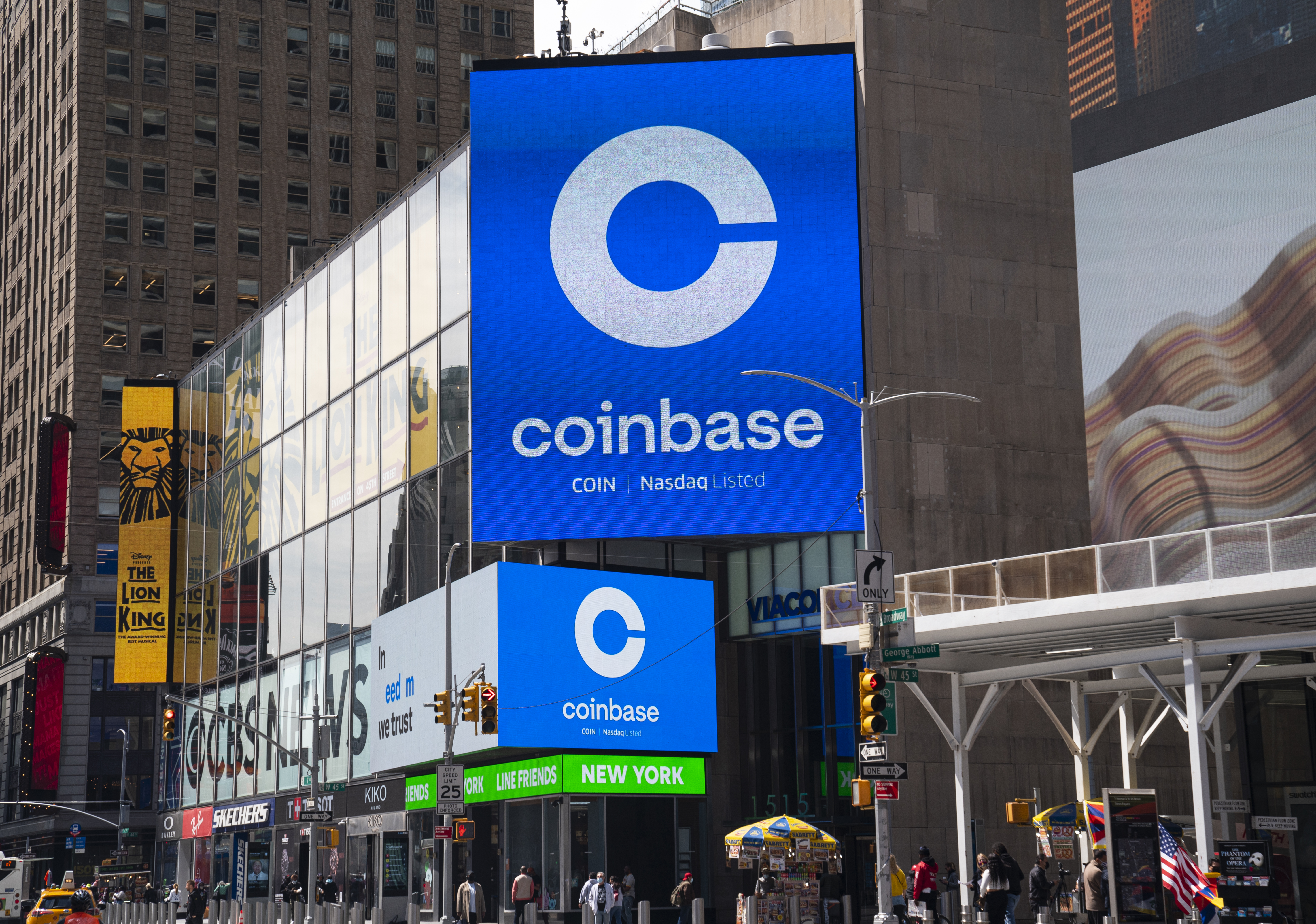 <p>Monitors display Coinbase signage during the company's initial public offering at the Nasdaq market site April 14, 2021 in New York City.</p>