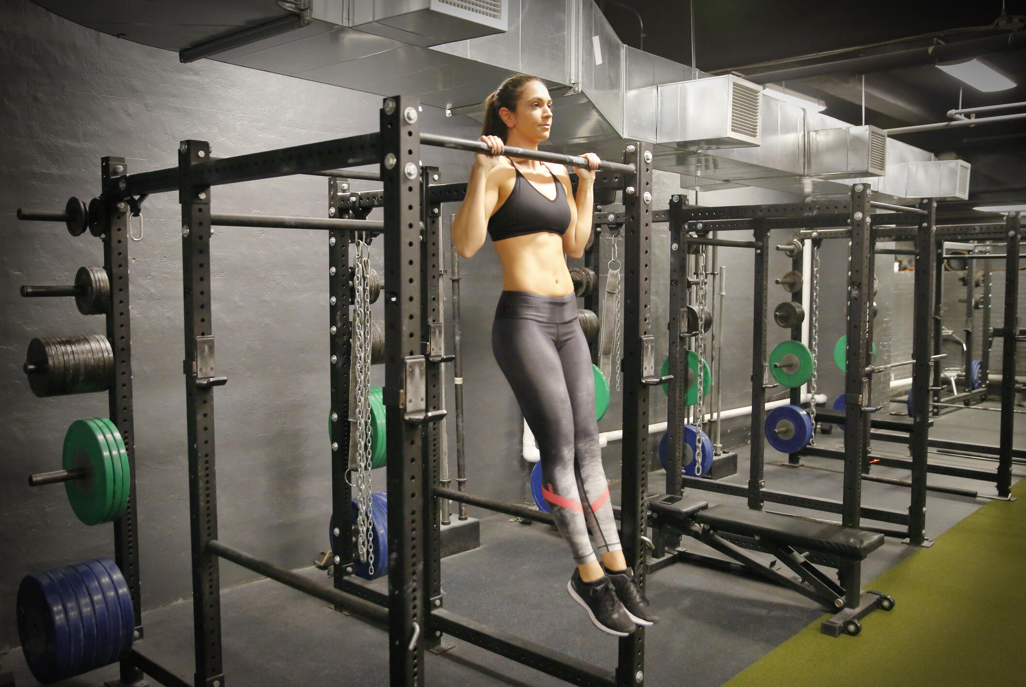 woman doing pull-ups in a gym