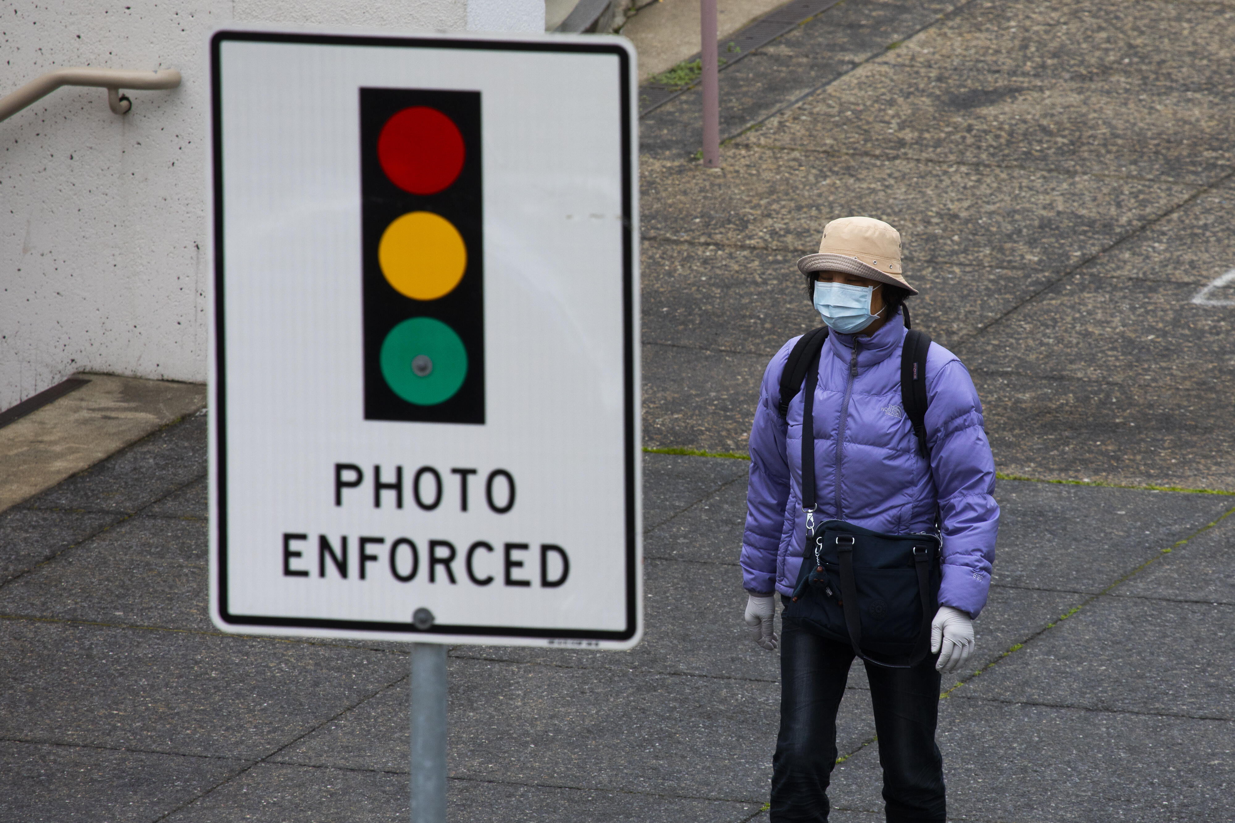"""Person wearing a face mask next to a stoplight sign that reads """"photo enforced"""""""