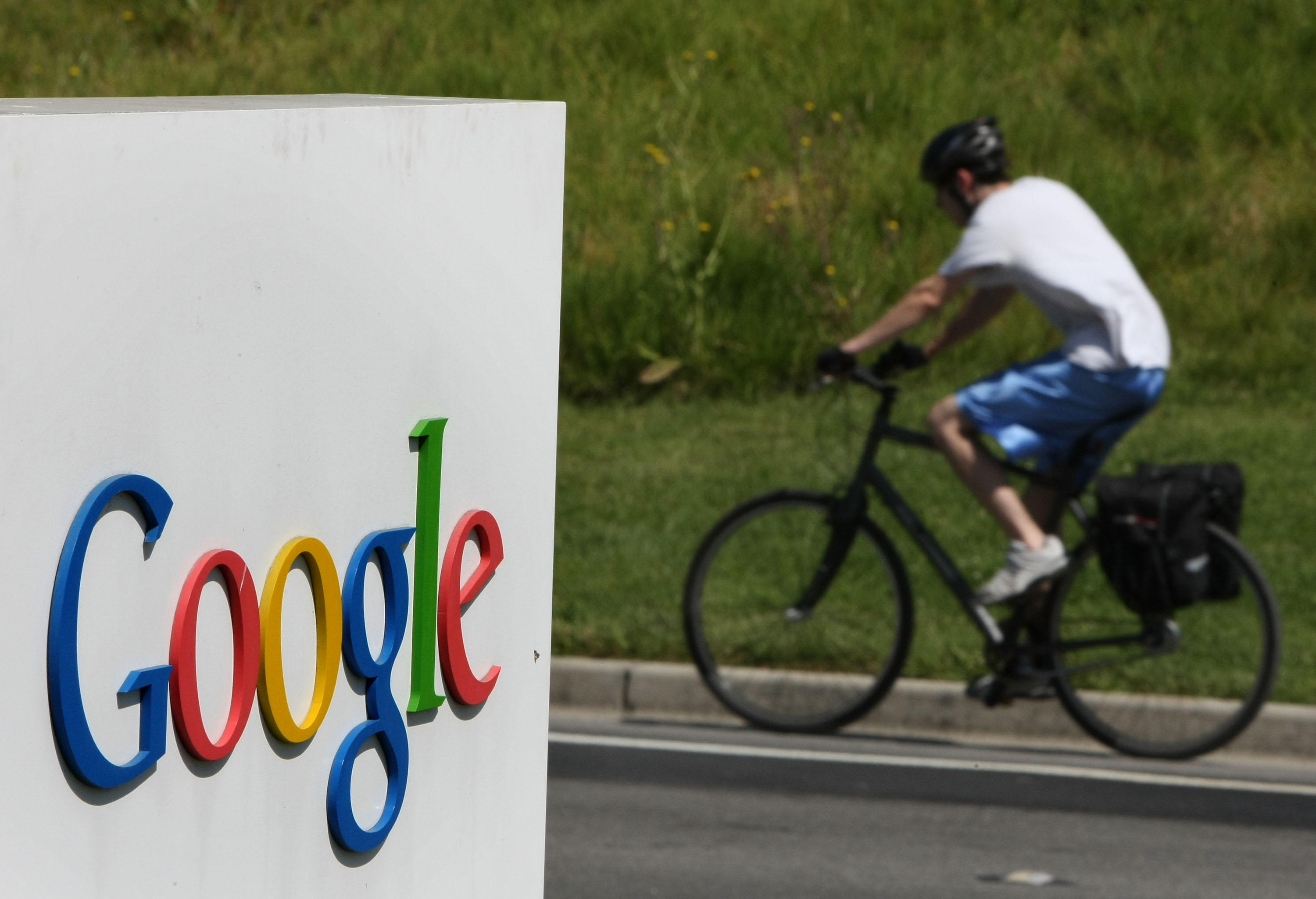Cyclist rides past Google sign