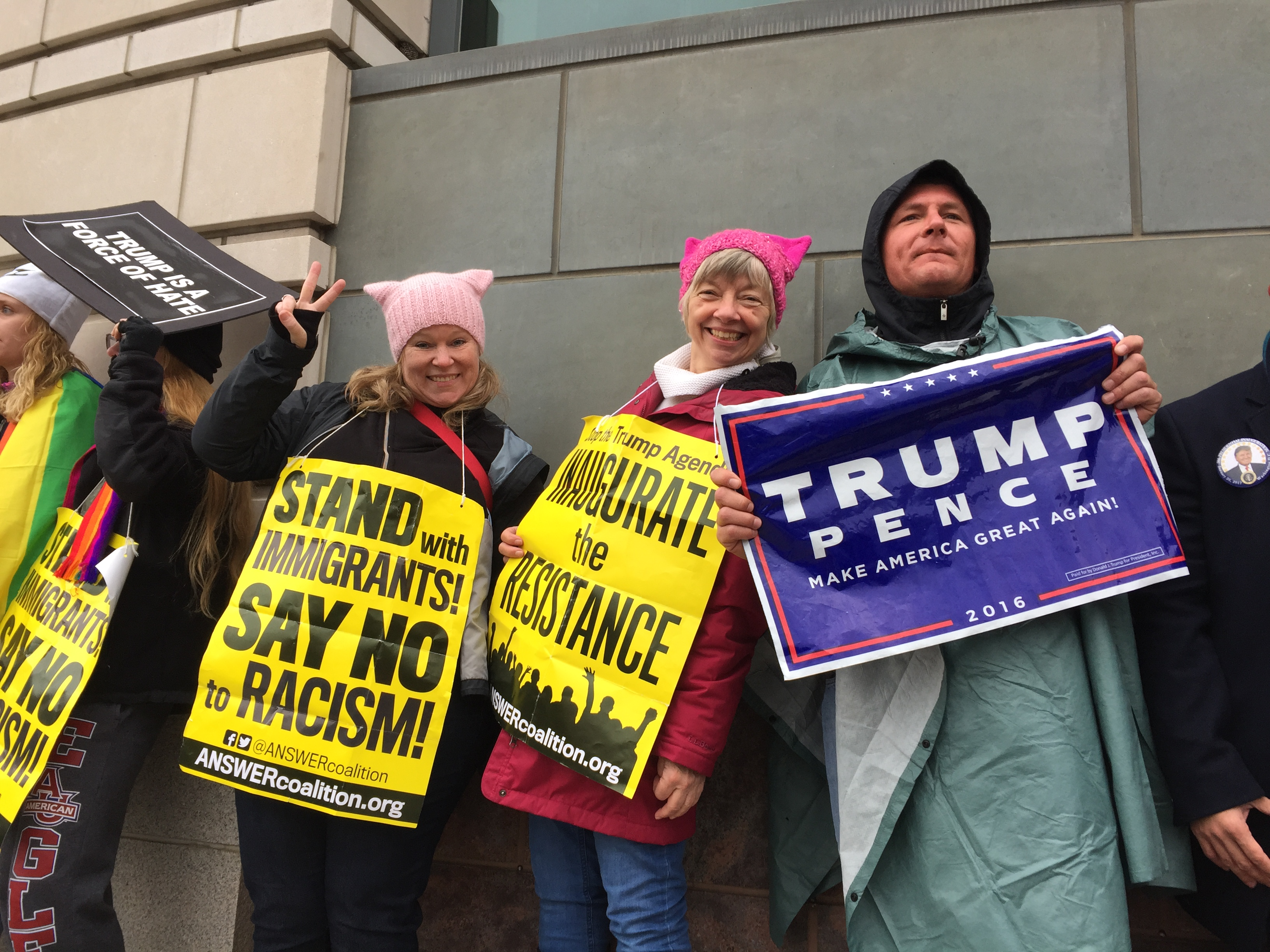 Amy McColm, 44, (left) and Chris Hinds, 68, (middle) of Tacoma, Washington, traveled to Washington, DC, for the Women's March. They stand alongside Trump supporter James Burnett, 43, (right) of Portsmouth, Virginia, along the inaugural parade route on Pennsylvania Avenue.