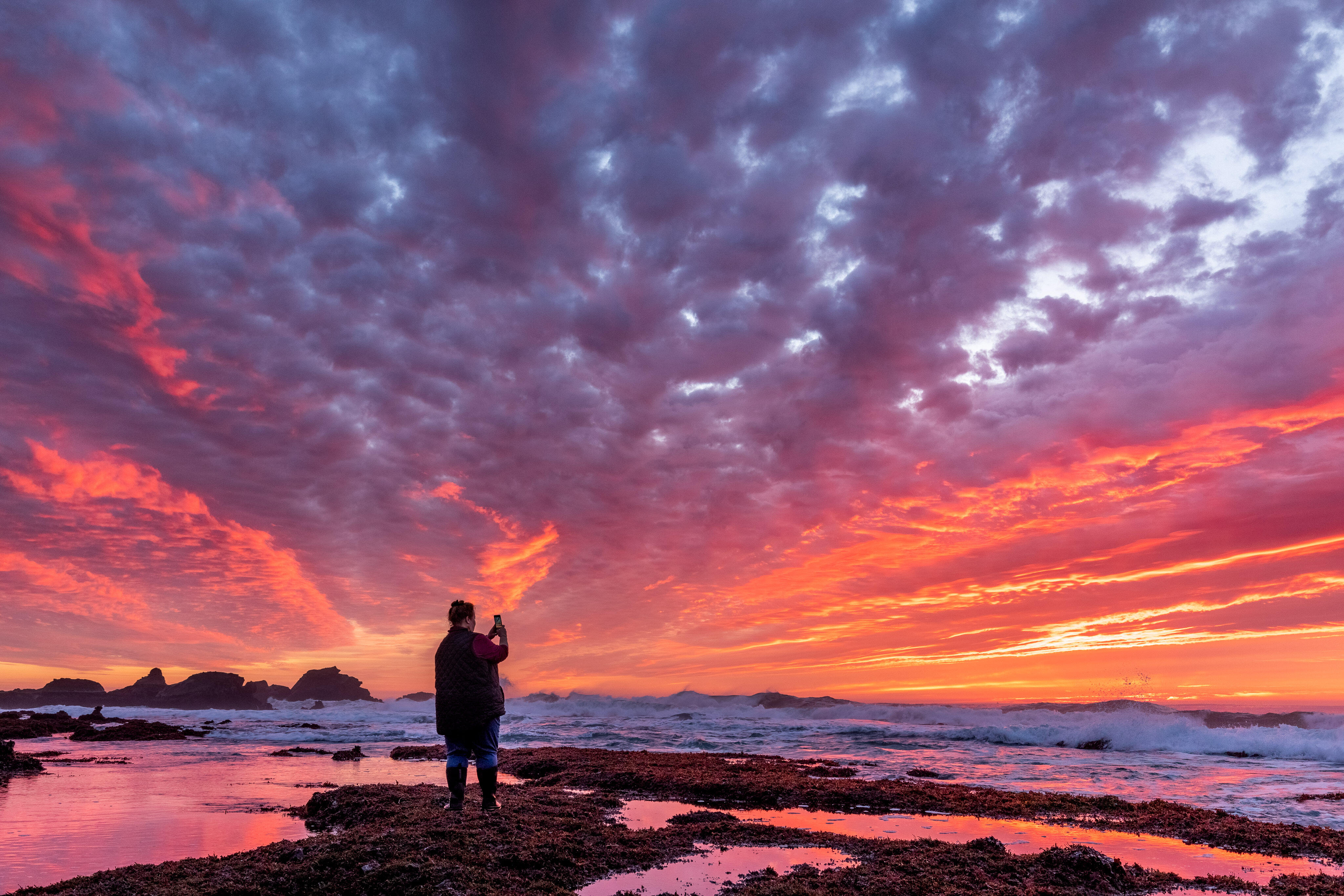 Alison Young photographs a brilliant sunset just after low tide at Pillar Point about 15 miles south of San Francisco. The rocks of Pillar Point just out into the Pacific Ocean toward the left; the Mavericks surfing competition takes place in the waves to