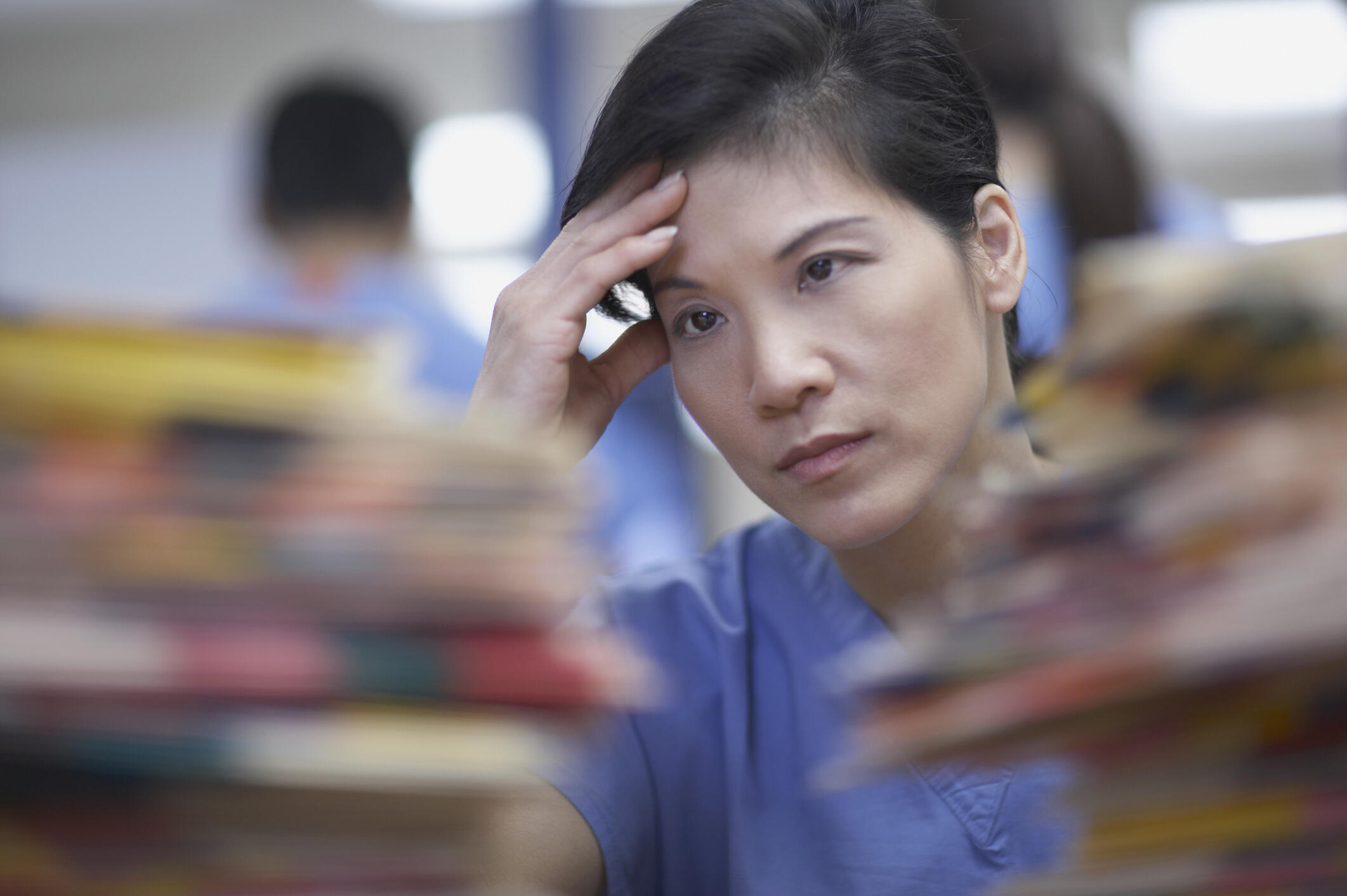 Asian female medical professional with hand on head - stock photo