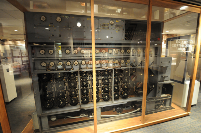 """Photograph of a U.S. Navy cryptanalytic bombe, the size of about three large refrigerators side by side, in a glass case. The machines """"worked primarily against the German Navy's four-rotor Enigmas."""