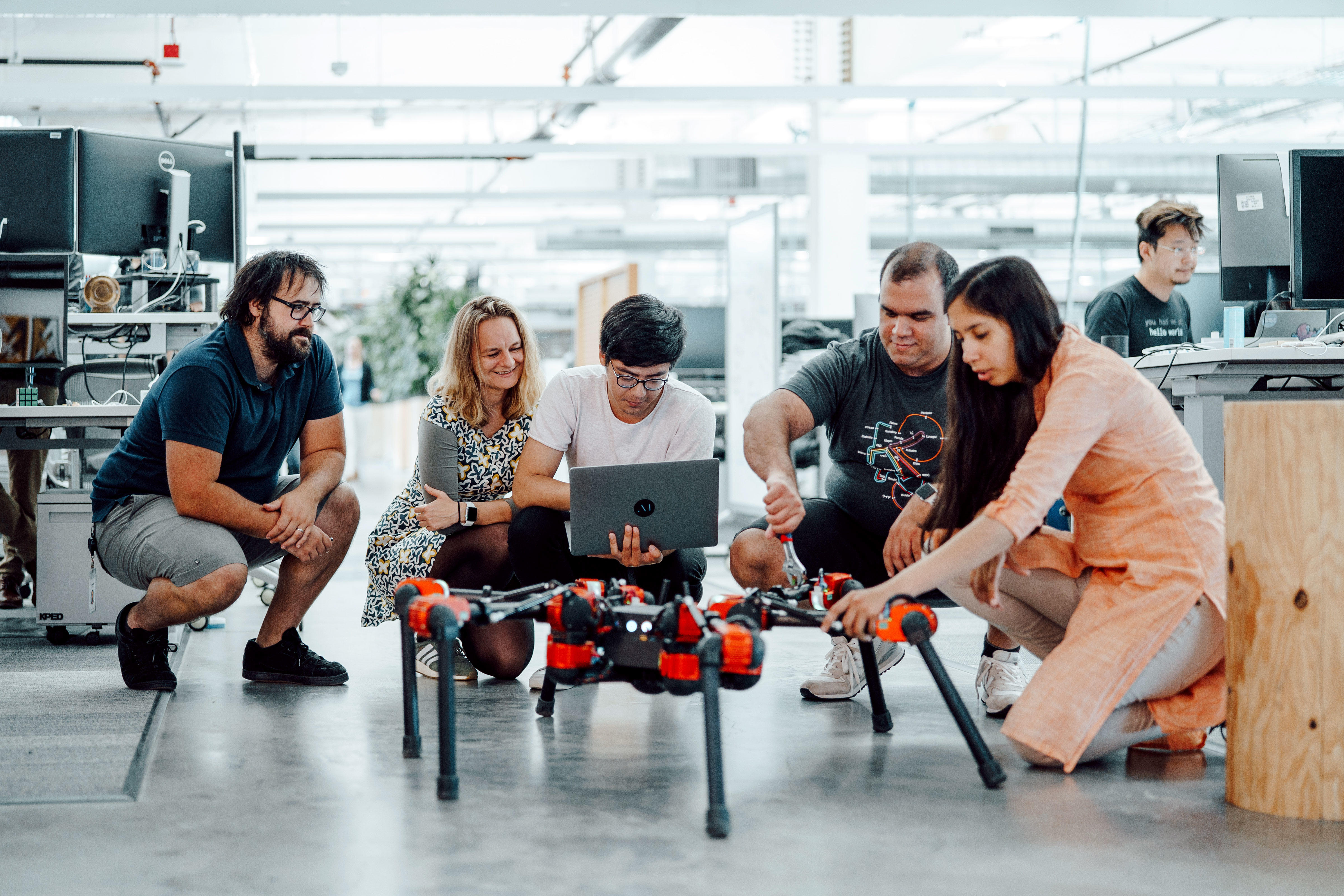Facebook AI researchers in Menlo Park with Daisy, a hexapod robot learning to walk. From left: Roberto Calandra, research scientist; Franziska Meier, research scientist; Yixin Lin, research engineer; Omry Yadan, software engineer; Akshara Rai, research scientist.